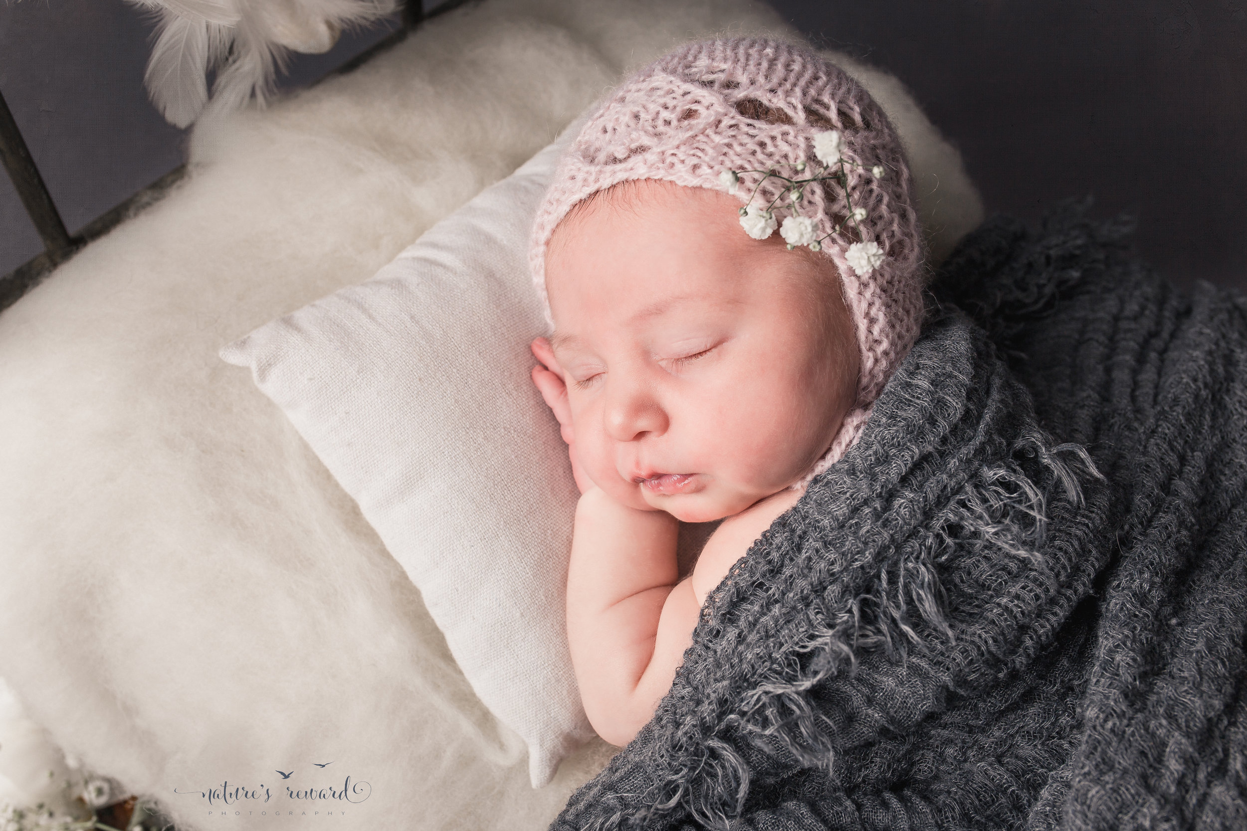Newborn baby portrait in greys, whites and soft pink, laying on a doll bed.A Portrait By Nature's Reward Photography, a San Bernardino Family, Child, and Newborn Baby Photographer.