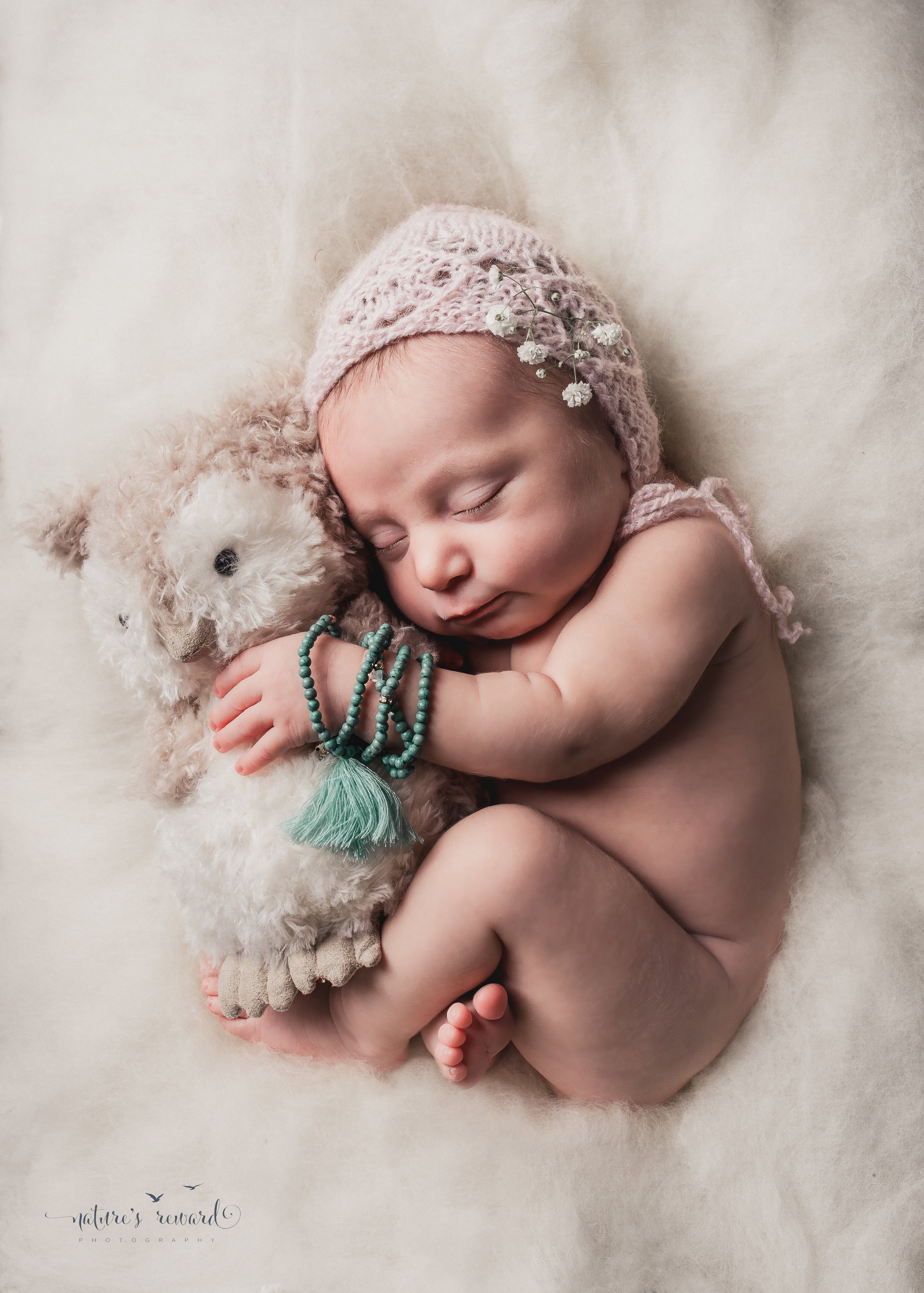 Newborn baby portrait in whites and soft pink, laying on a doll bed holding her owl.A Portrait By Nature's Reward Photography, a San Bernardino Family, Child, and Newborn Baby Photographer.