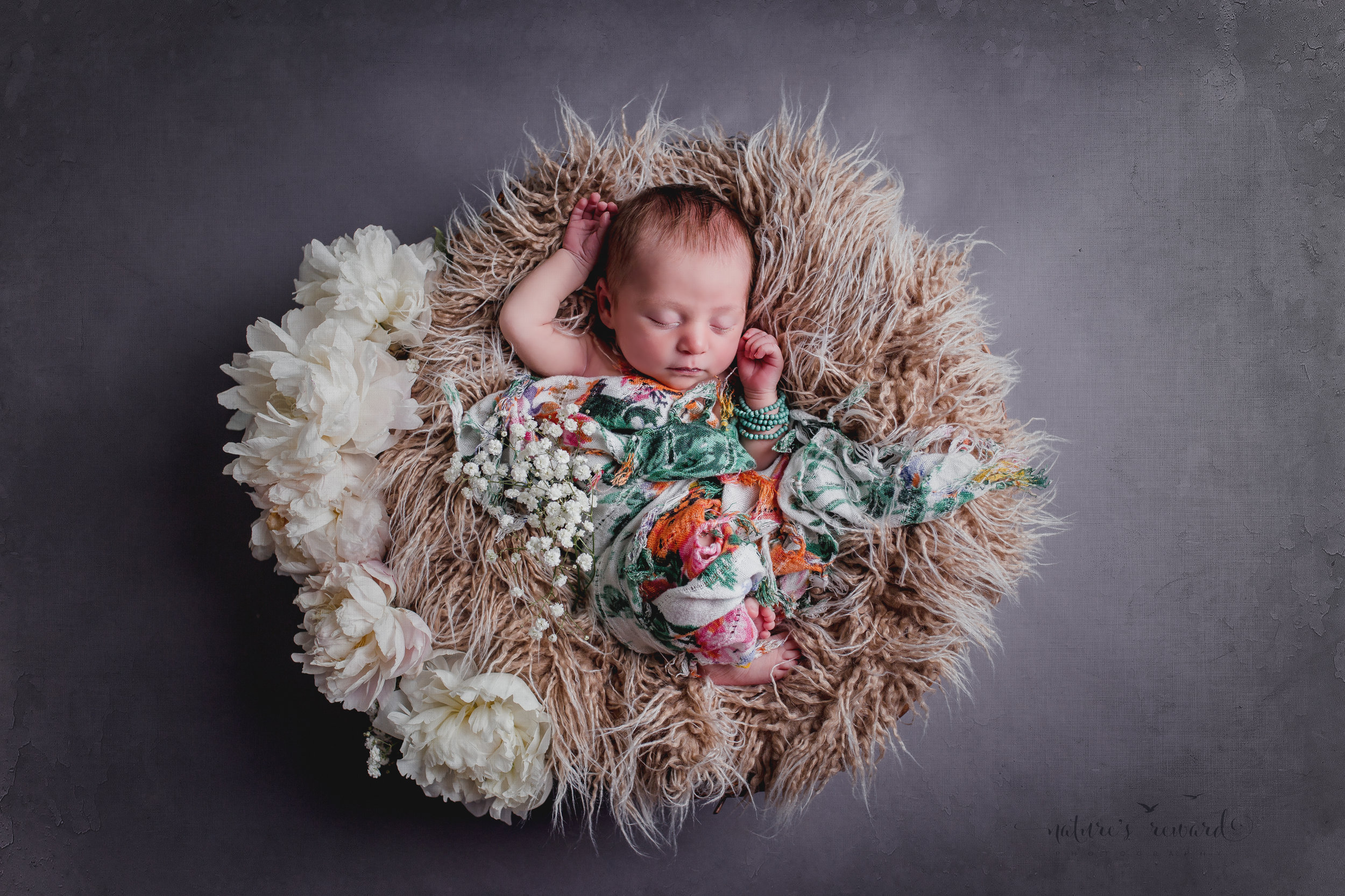 Newborn baby portrait in whites and soft teal, laying on a bed of fur draped in floral.A Portrait By Nature's Reward Photography, a San Bernardino Family, Child, and Newborn Baby Photographer.