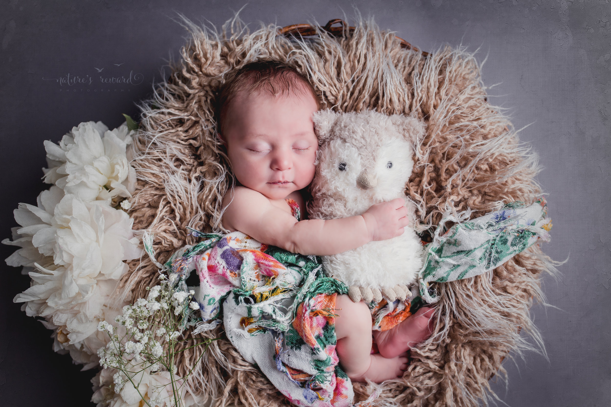 Newborn baby portrait in whites and soft teal, laying on a bed of fur draped in floral holding her owl.A Portrait By Nature's Reward Photography, a San Bernardino Family, Child, and Newborn Baby Photographer.