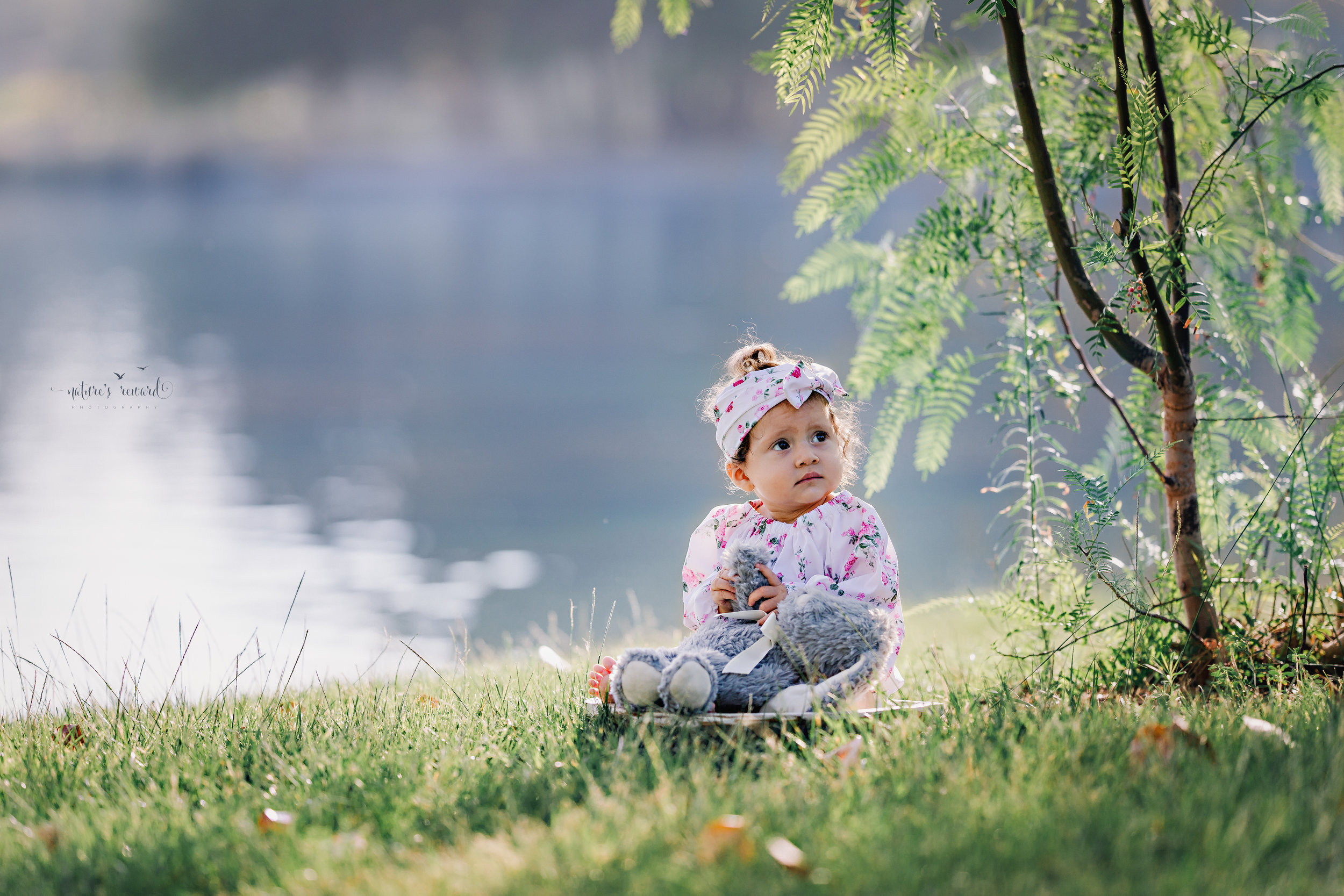 Beautiful Baby in a white floral romper during her sitter session near a lake in this portrait by Nature's Reward Photography.