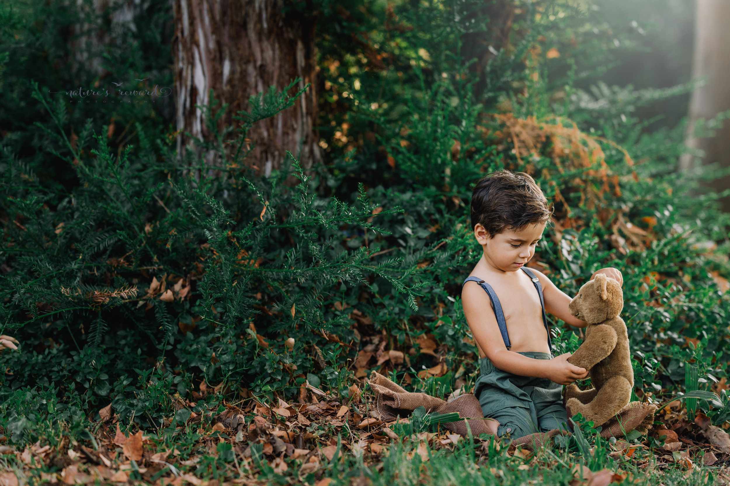 Beautiful toddler baby boy wearing the cutest pair of pants and suspenders playing with his teddy in this vintage inspired portrait by Nature's Reward Photography