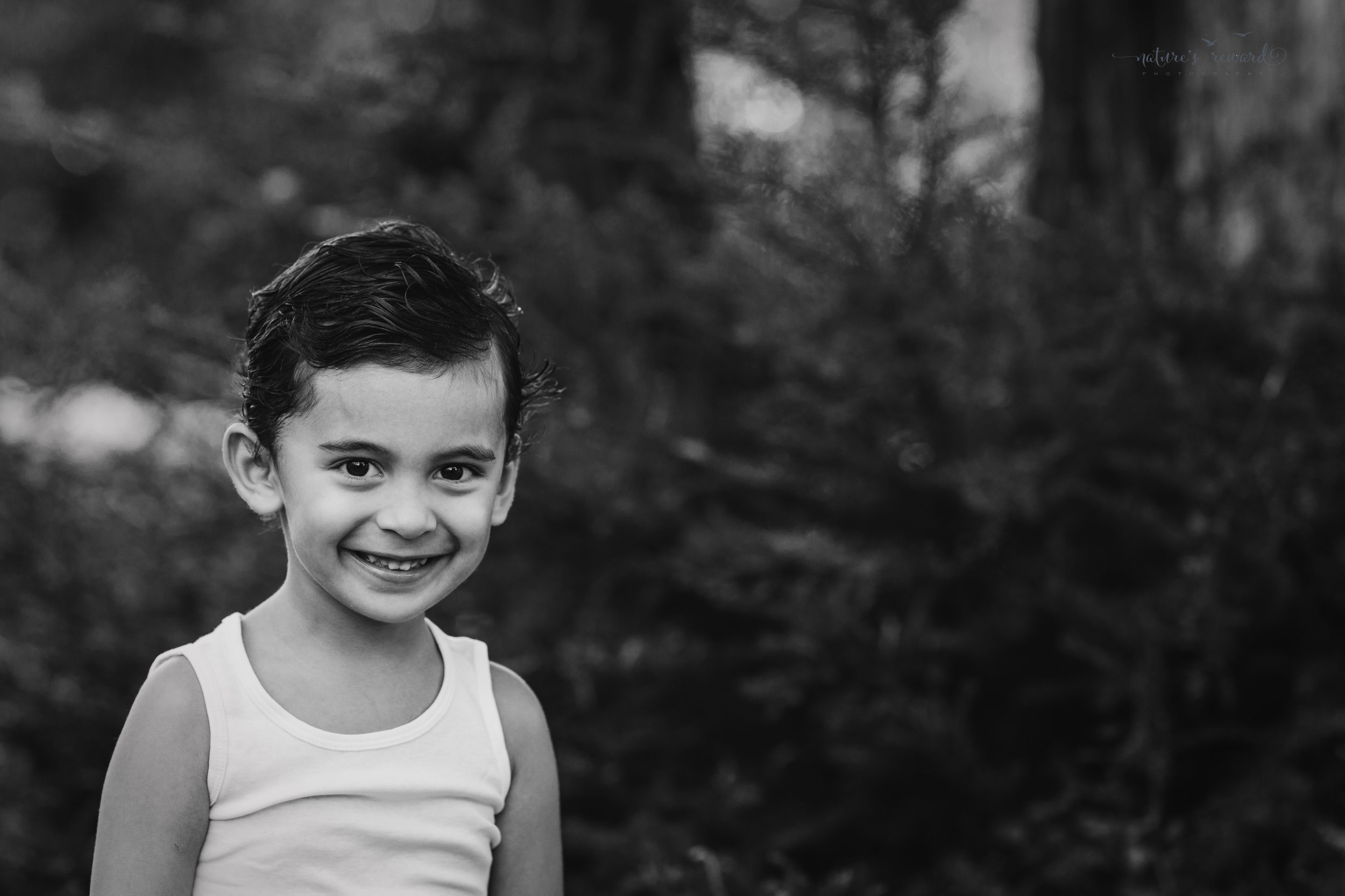 Close up black and white portrait of a young boy by Nature's Reward Photography