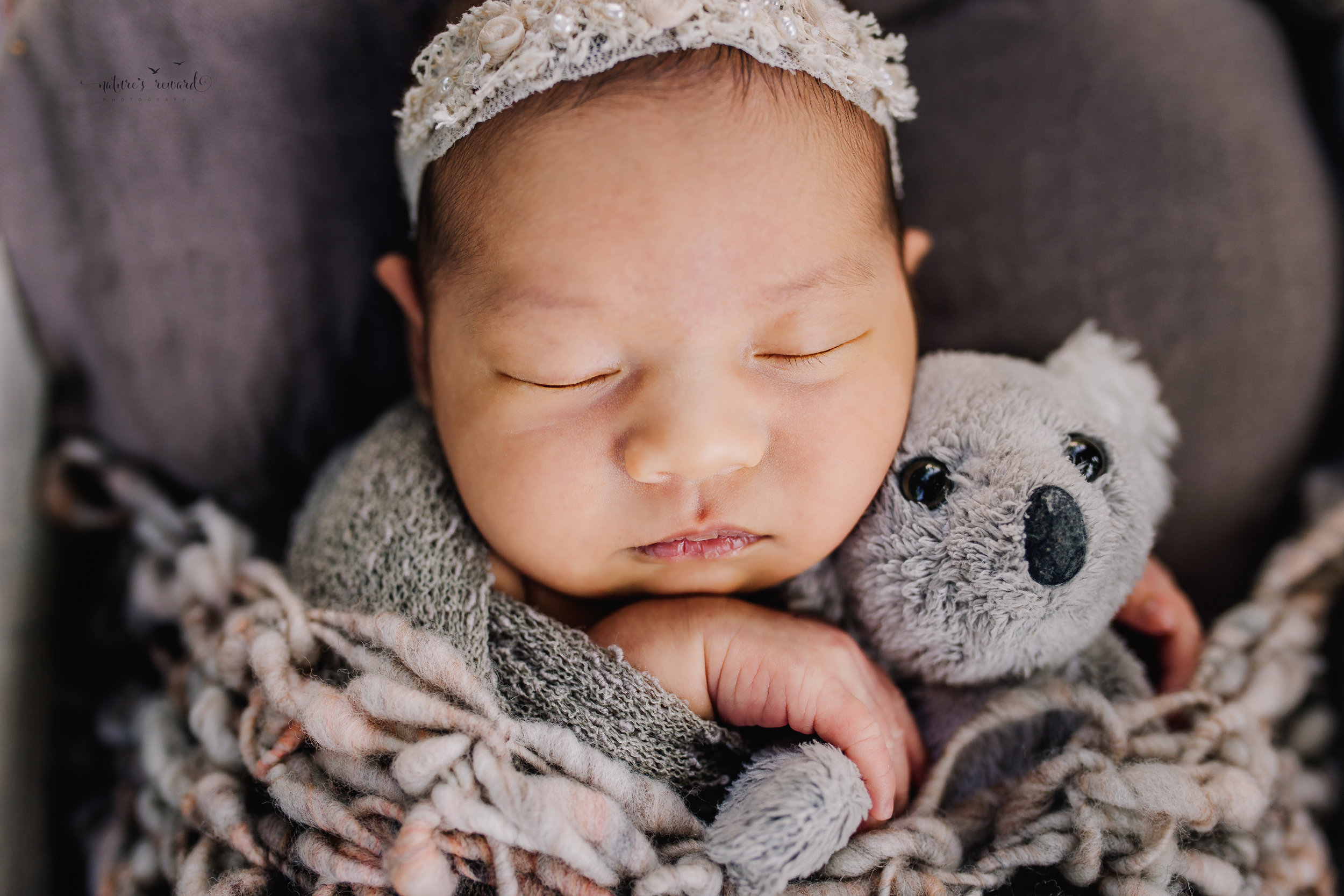 Gorgeous baby newborn girl swaddled in neutral wearing a white tie back and in a garden surrounded by lush greens in this portrait by Nature's Reward Photography