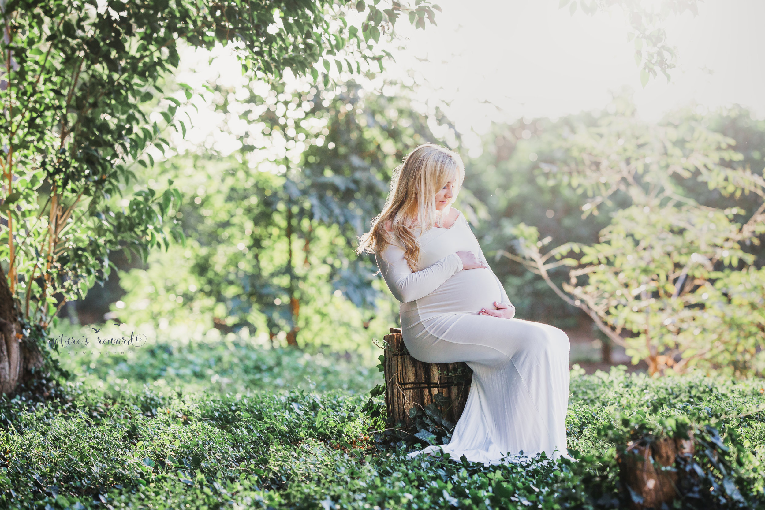 Stunning Expecting mother in a white gown in this ethereal maternity portrait by Nature's Reward Photography