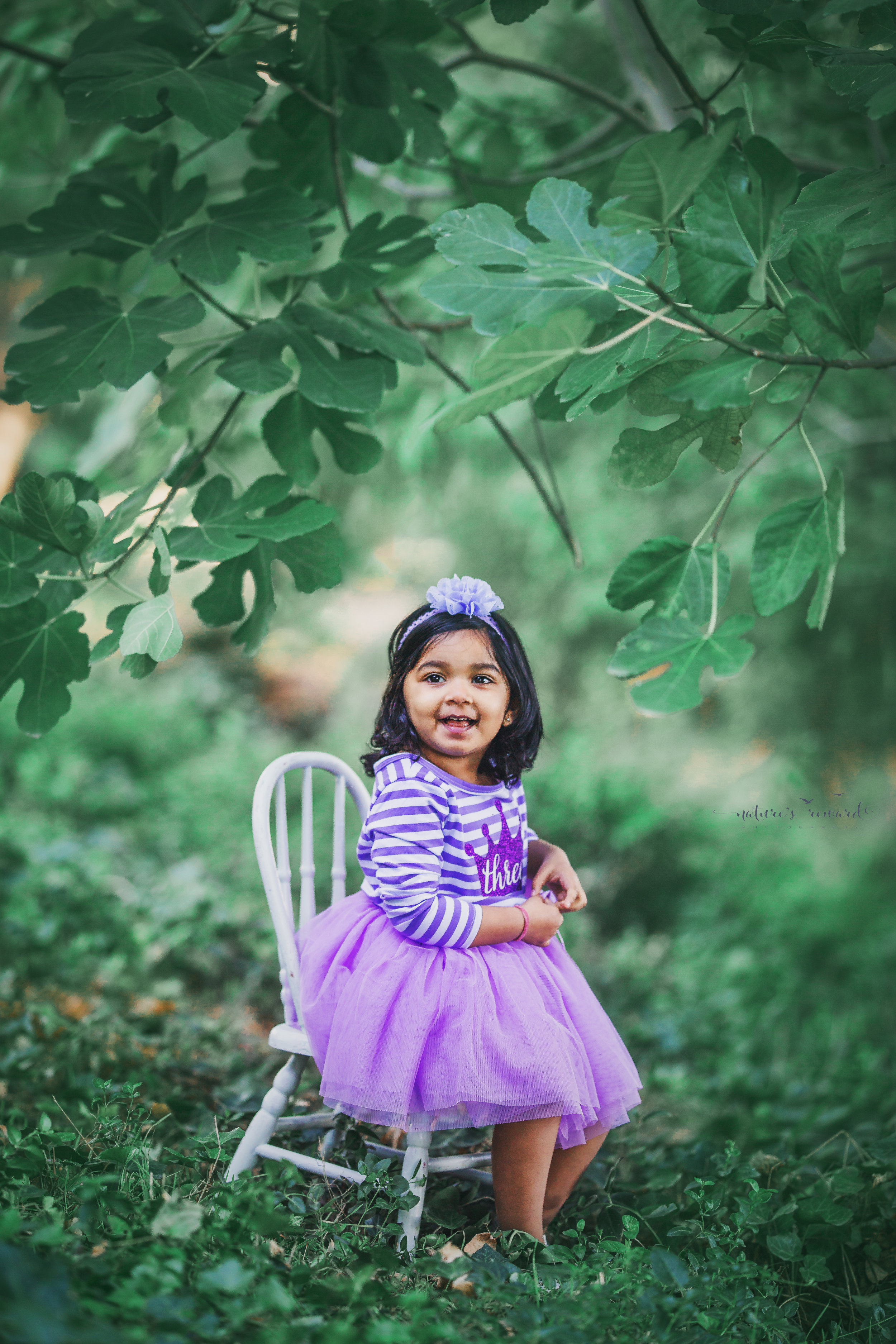 She is 3 birthday photography session while wearing a purple striped and tulle bottom dress sitting on a chair in a magical green park setting a portrait by Nature's Reward Photography