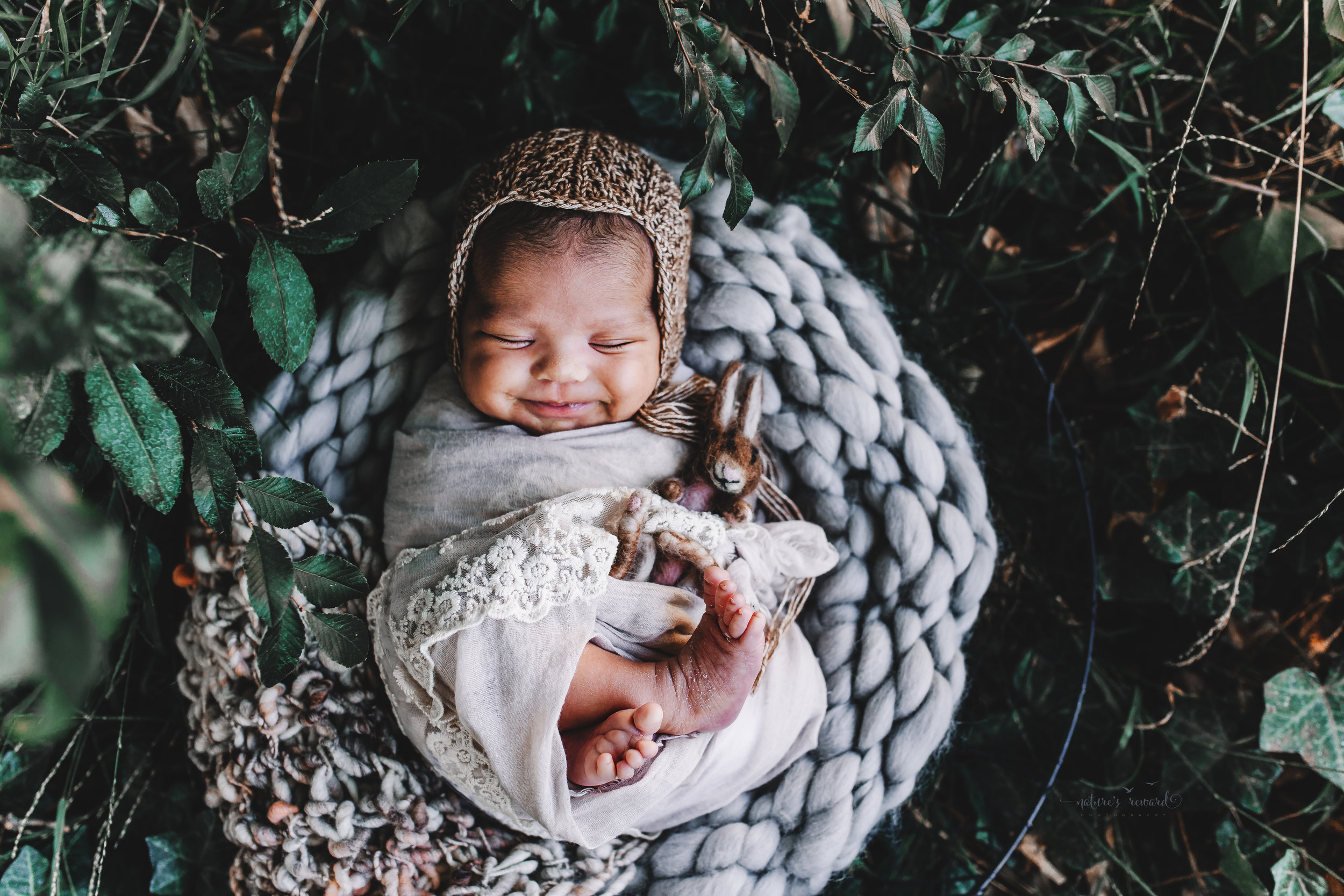 Newborn baby girl in tan lace swaddle and a brown knit bonnets holding a sweet felted rabbit smiling in the garden- a portrait by Nature's Reward Photography