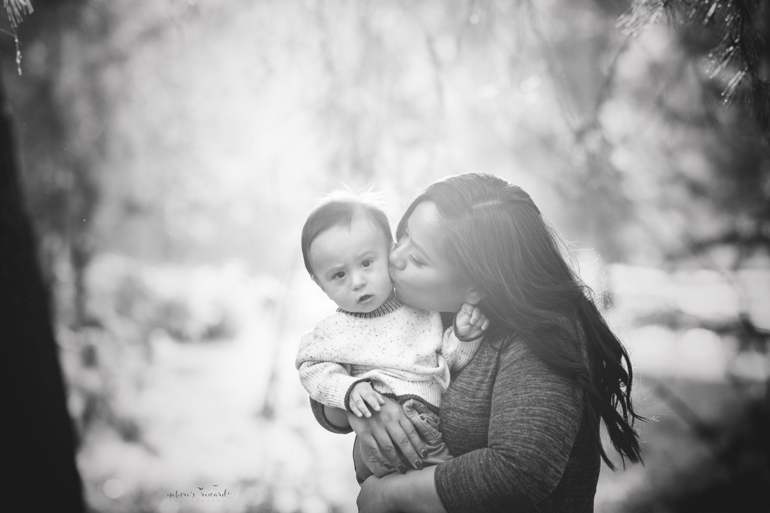 A black and white portrait of aunty giving kisses- by Nature's Reward Photography
