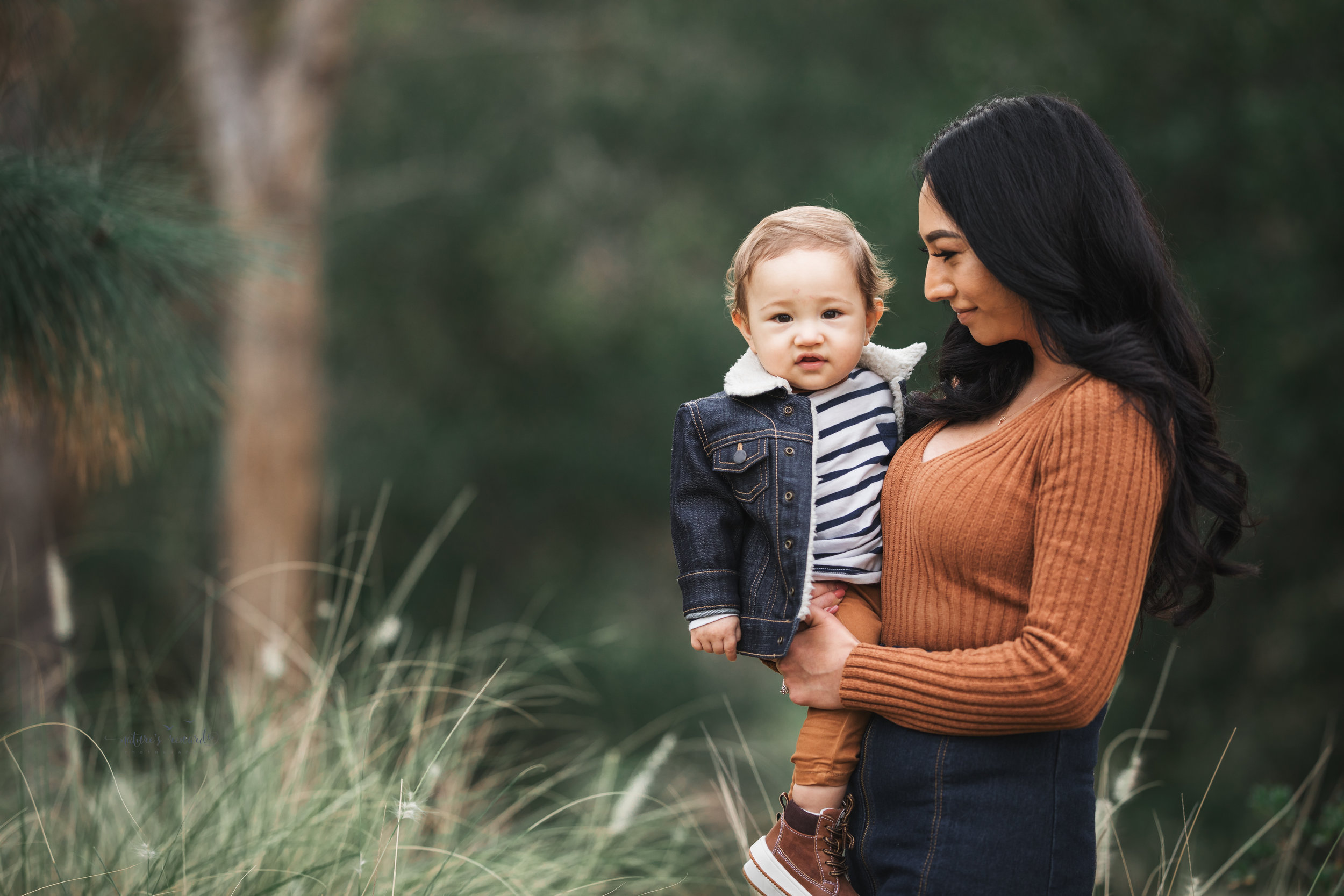 Baby boy in tans and blues  with his mother in a portrait by Nature's reward Photography