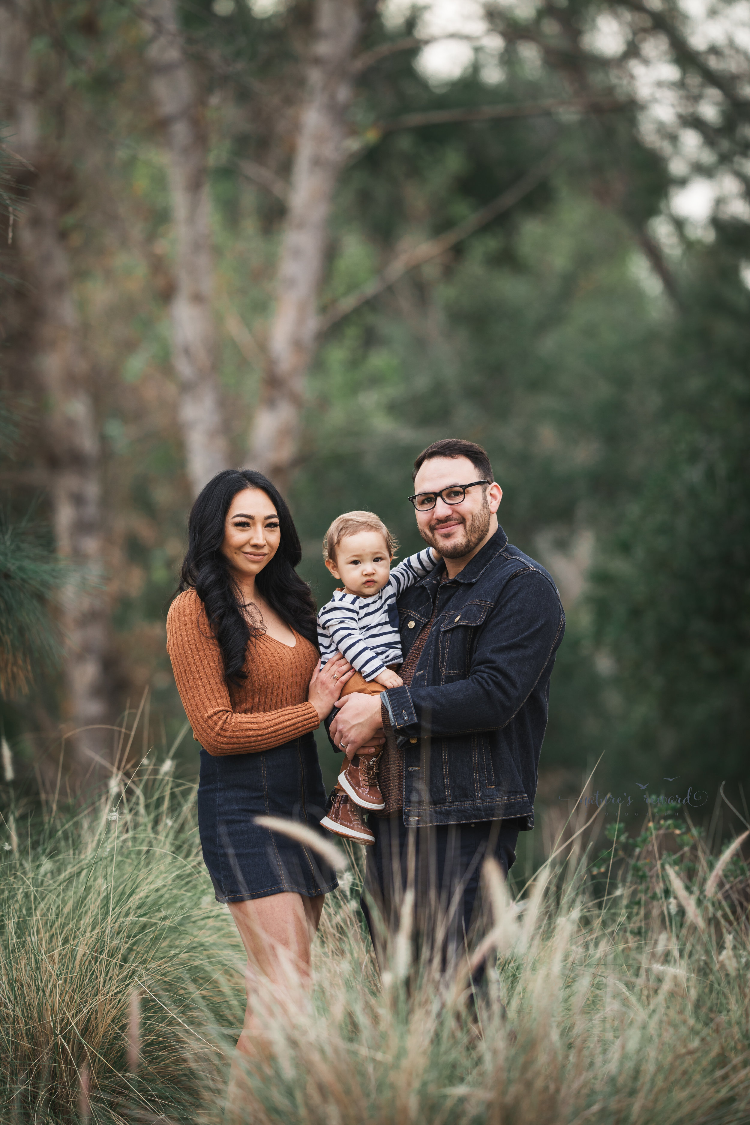 Baby boy in tans and blues with his mother and father in a portrait by Nature's reward Photography