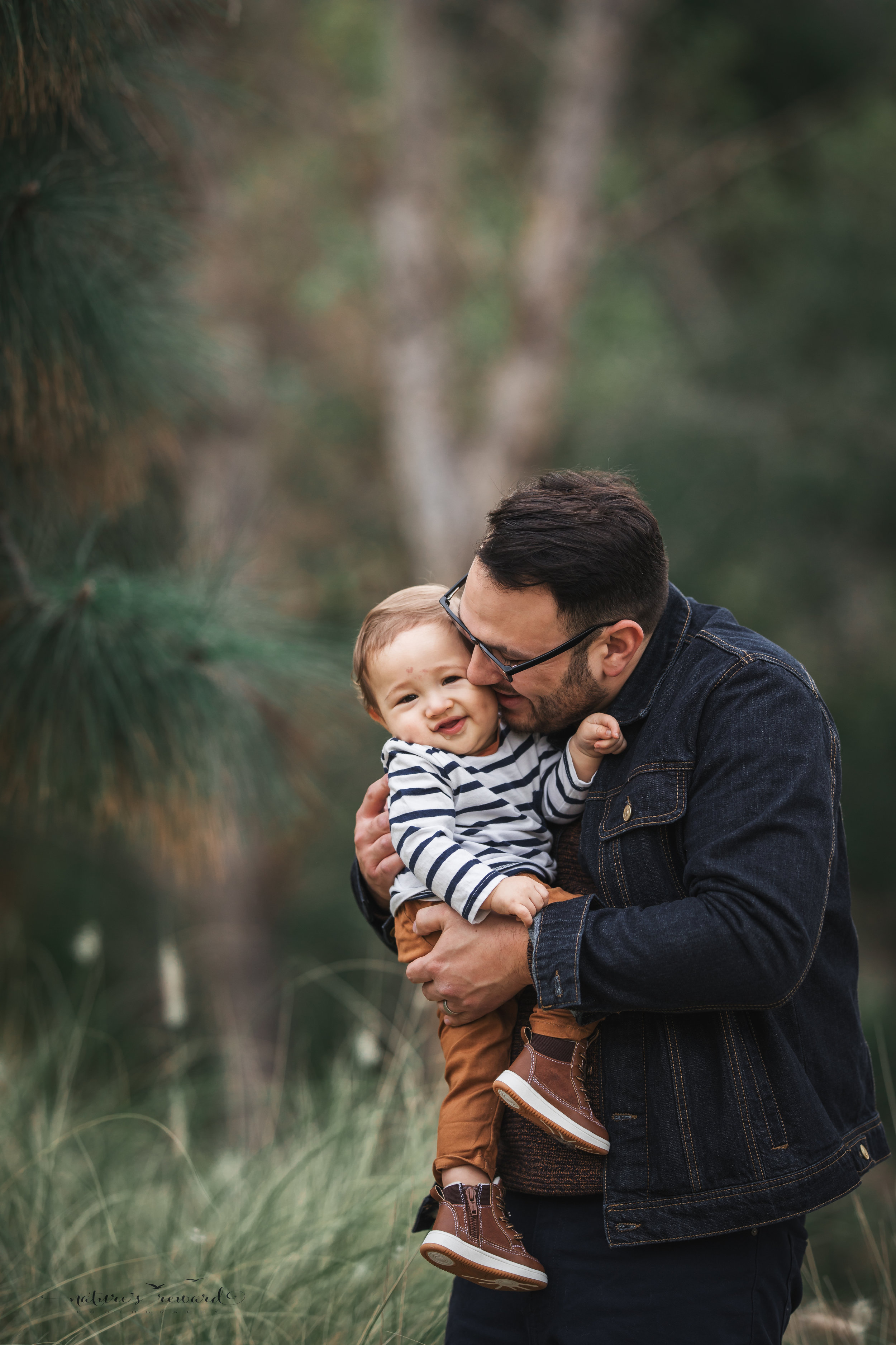 Baby boy in tans and blues with his  father in a portrait by Nature's reward Photography