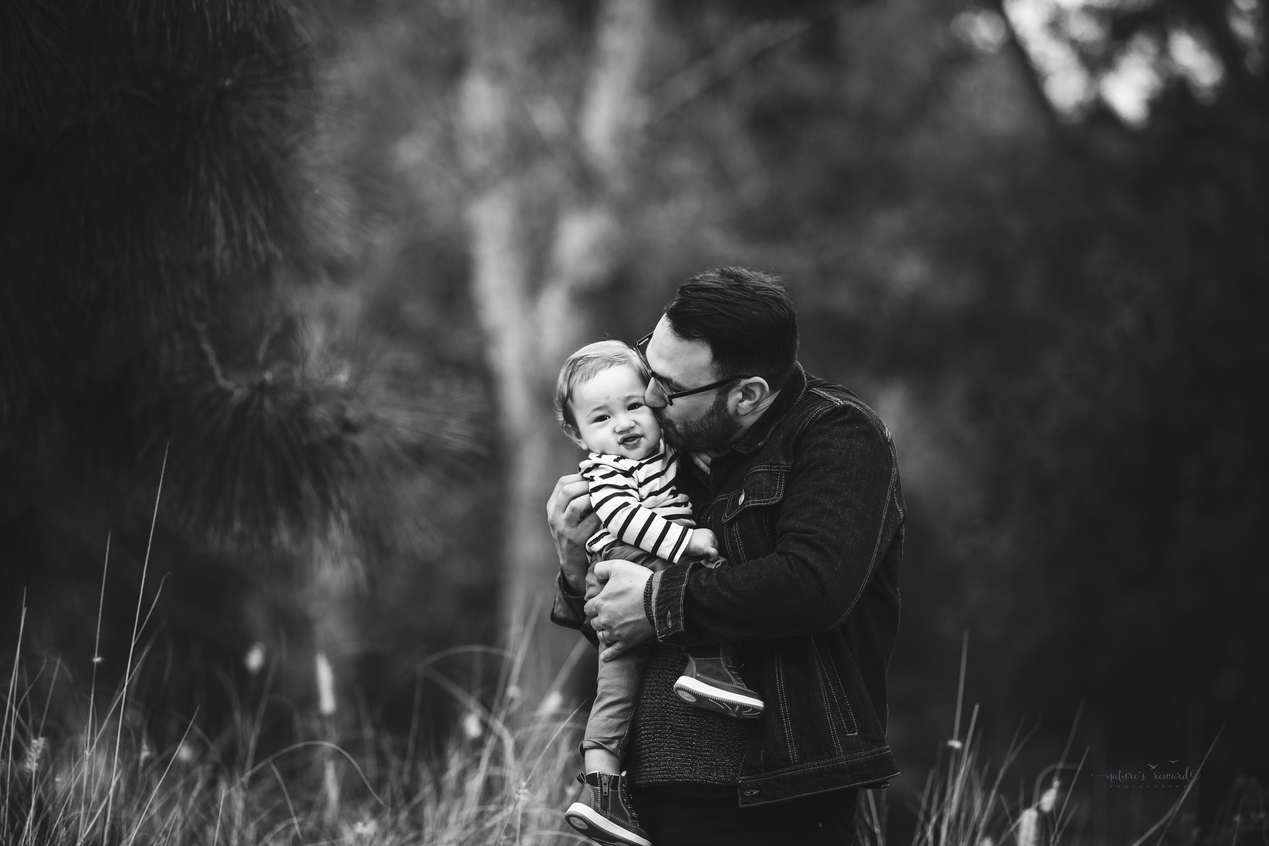 Baby boy in tans and blues with his father in a black and white portrait by Nature's reward Photography