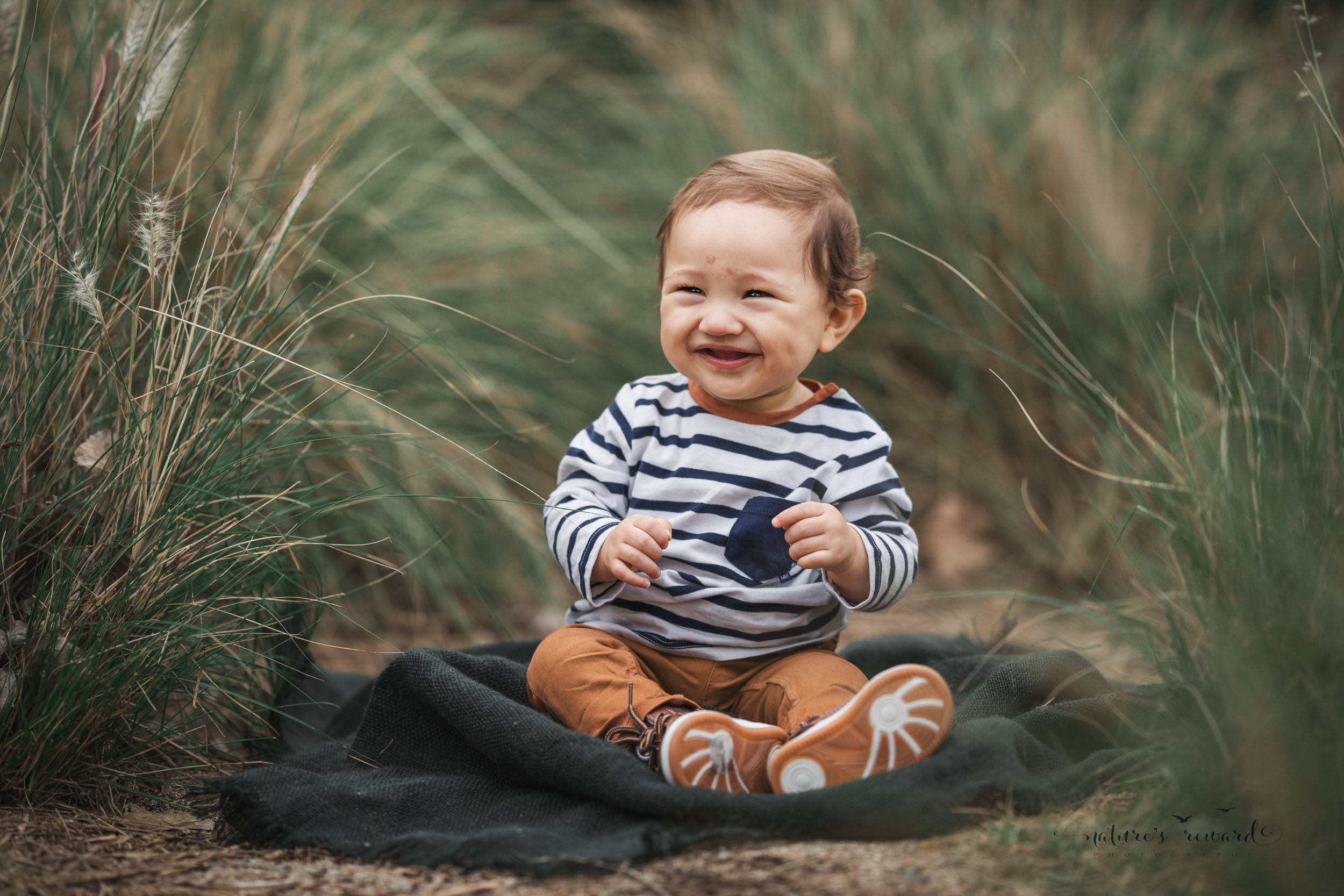 Beautiful baby boy in tans and a white and blue striped shirt in this portrait by Nature's Reward photography