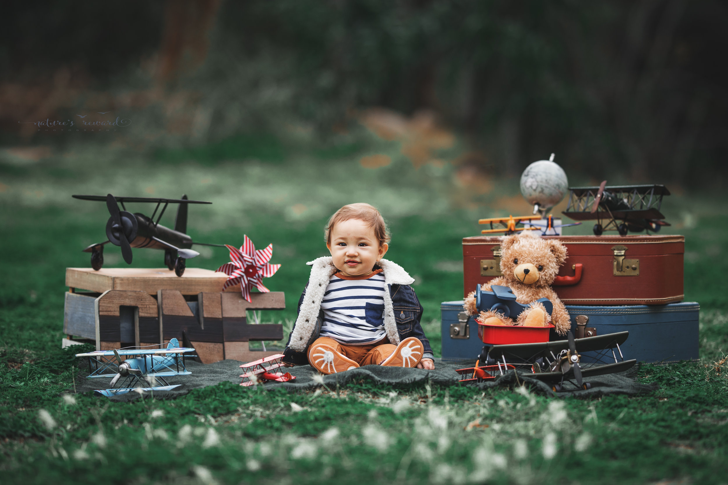 Beautiful baby boy in tans and a white and blue striped shirt and jean jacket in his airplane themed cake smash set in this portrait by Nature's Reward photography