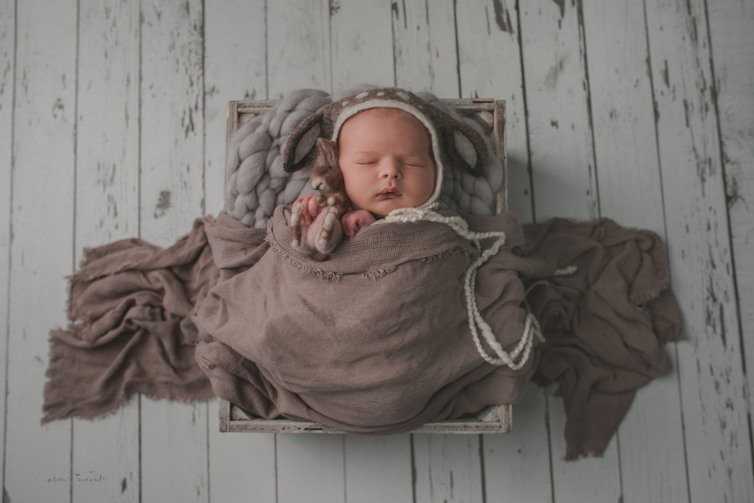 Newborn baby boy swaddled in white with brown scarf and wearing a deer bonnet, on a white wood floor, resting in a box, a portrait by Nature's Reward Photography
