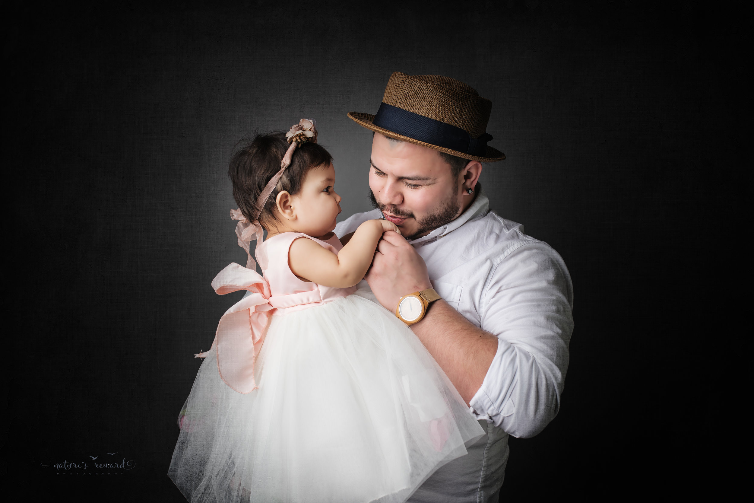 Father and daughter dressed in white on a grey background, a portrait by Nature's Reward Photography