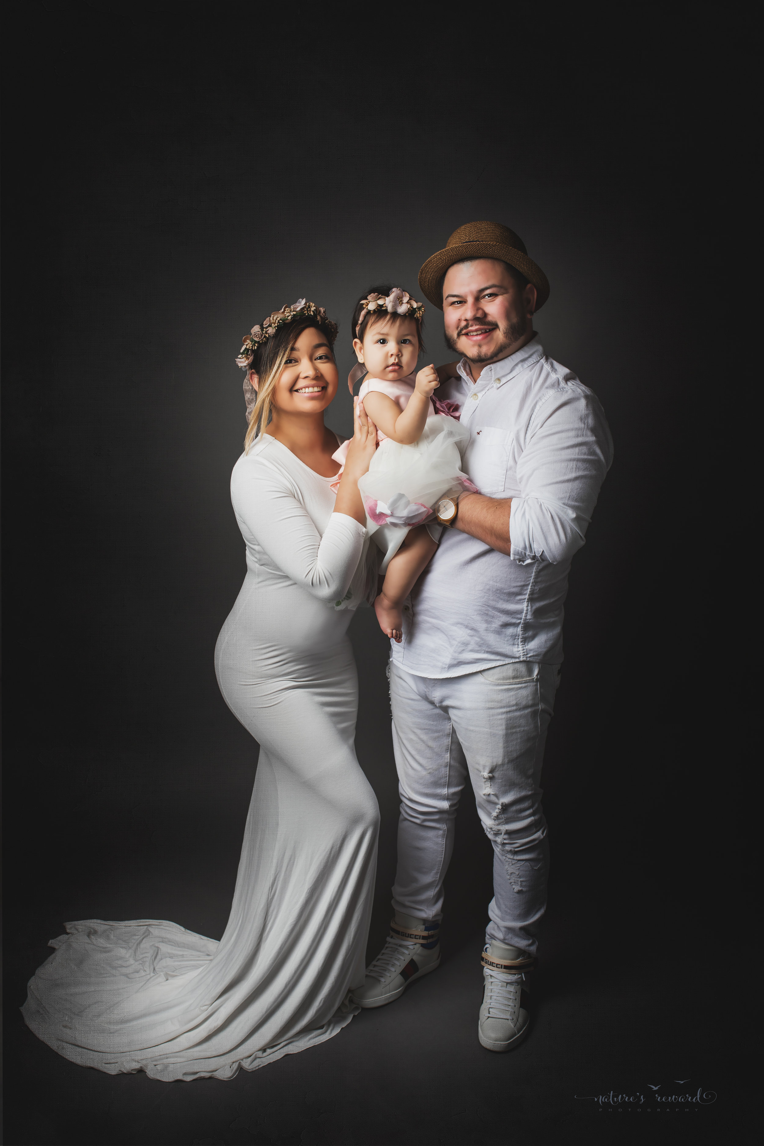 Mother, father and daughter dressed in white on a grey background, a portrait by Nature's Reward Photography