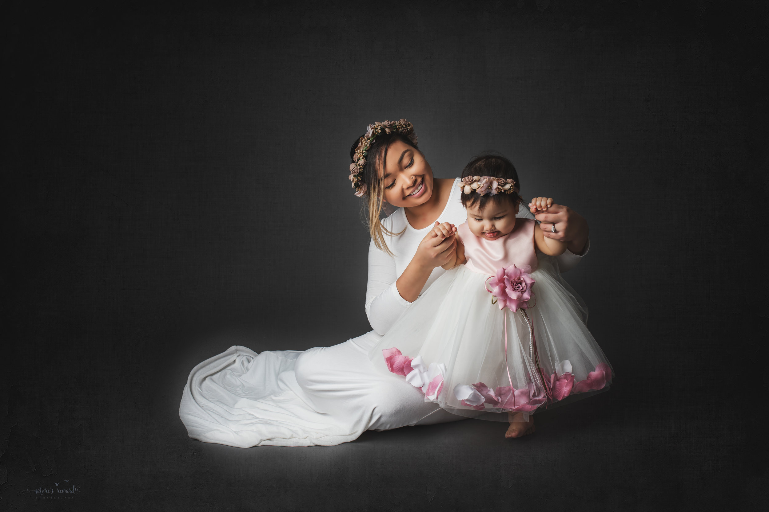 Mother and daughter dressed in white on a grey background, a portrait by Nature's Reward Photography