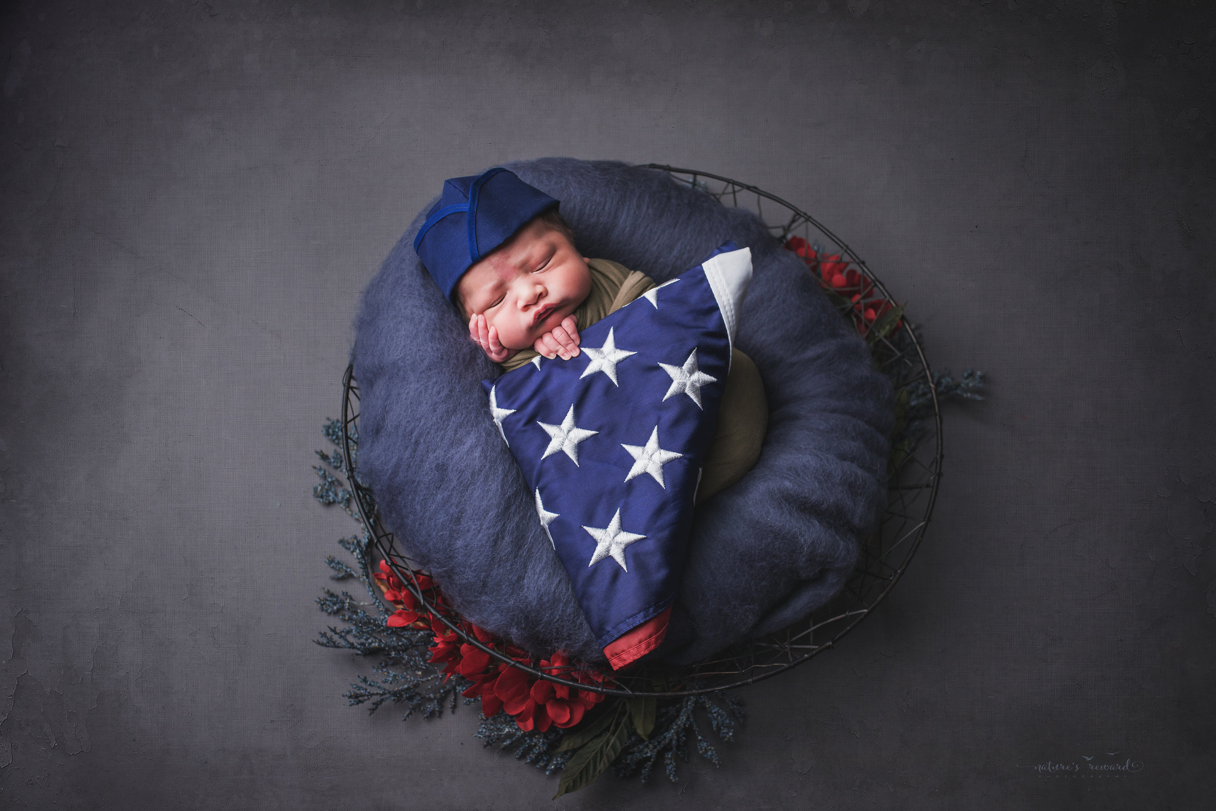 Wearing a service cap and holding an American flag, a swaddled newborn baby boy, a portrait by Nature's Reward Photography