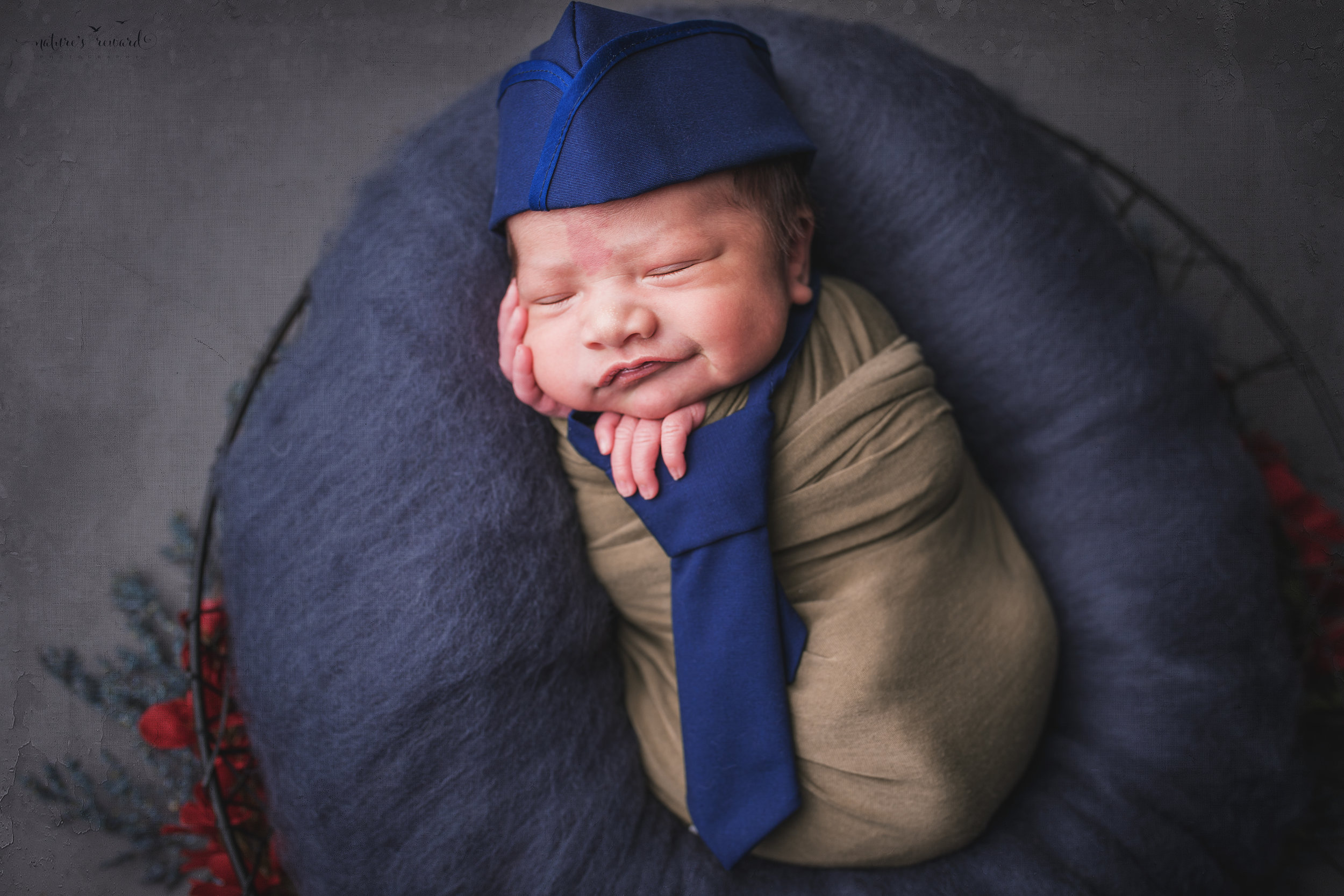 Swaddled in army green wearing a tie and service cap, a newborn portrait by Nature's Reward Photography