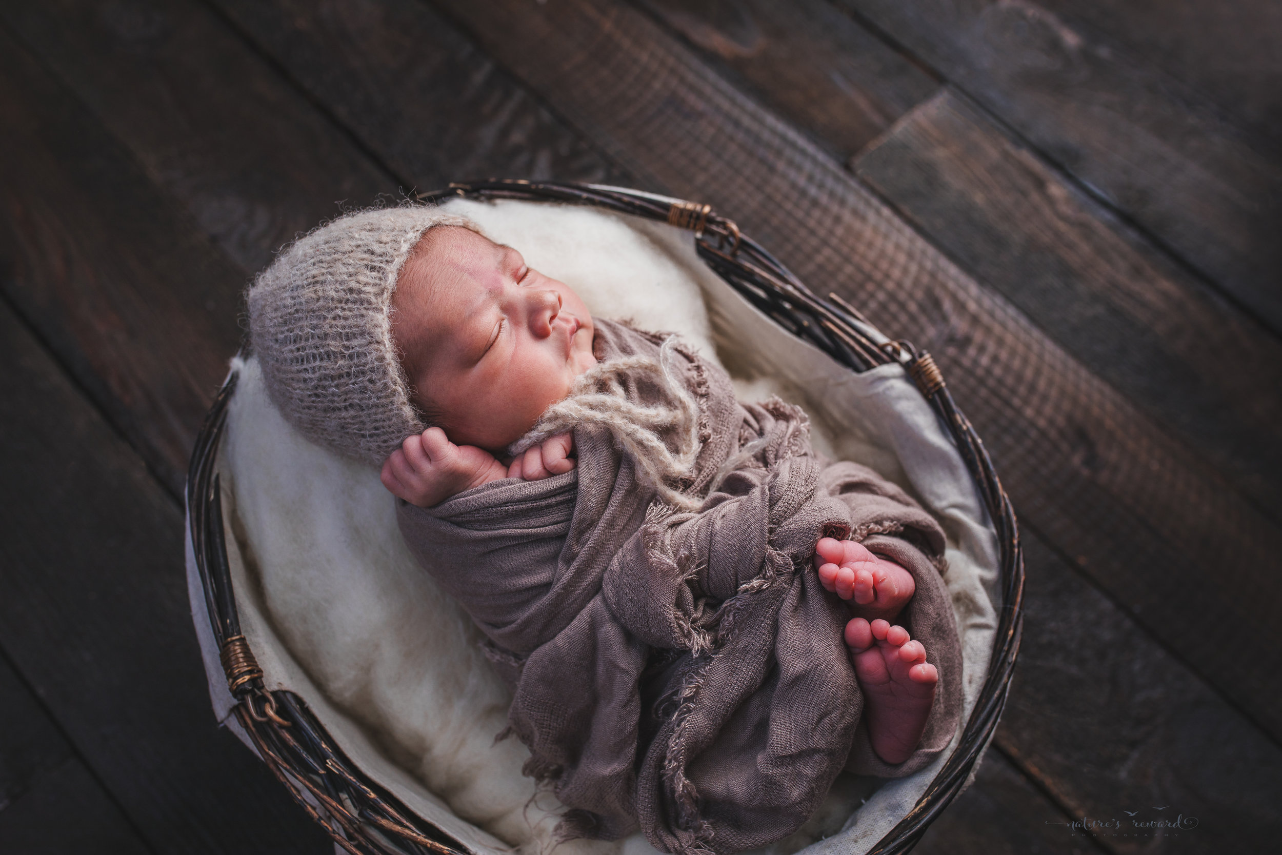 Newborn baby boy in a basket swaddled in tan wearing a tan bonnet with hands and feet out on a real wood floor, a portrait by Nature's Reward Photography