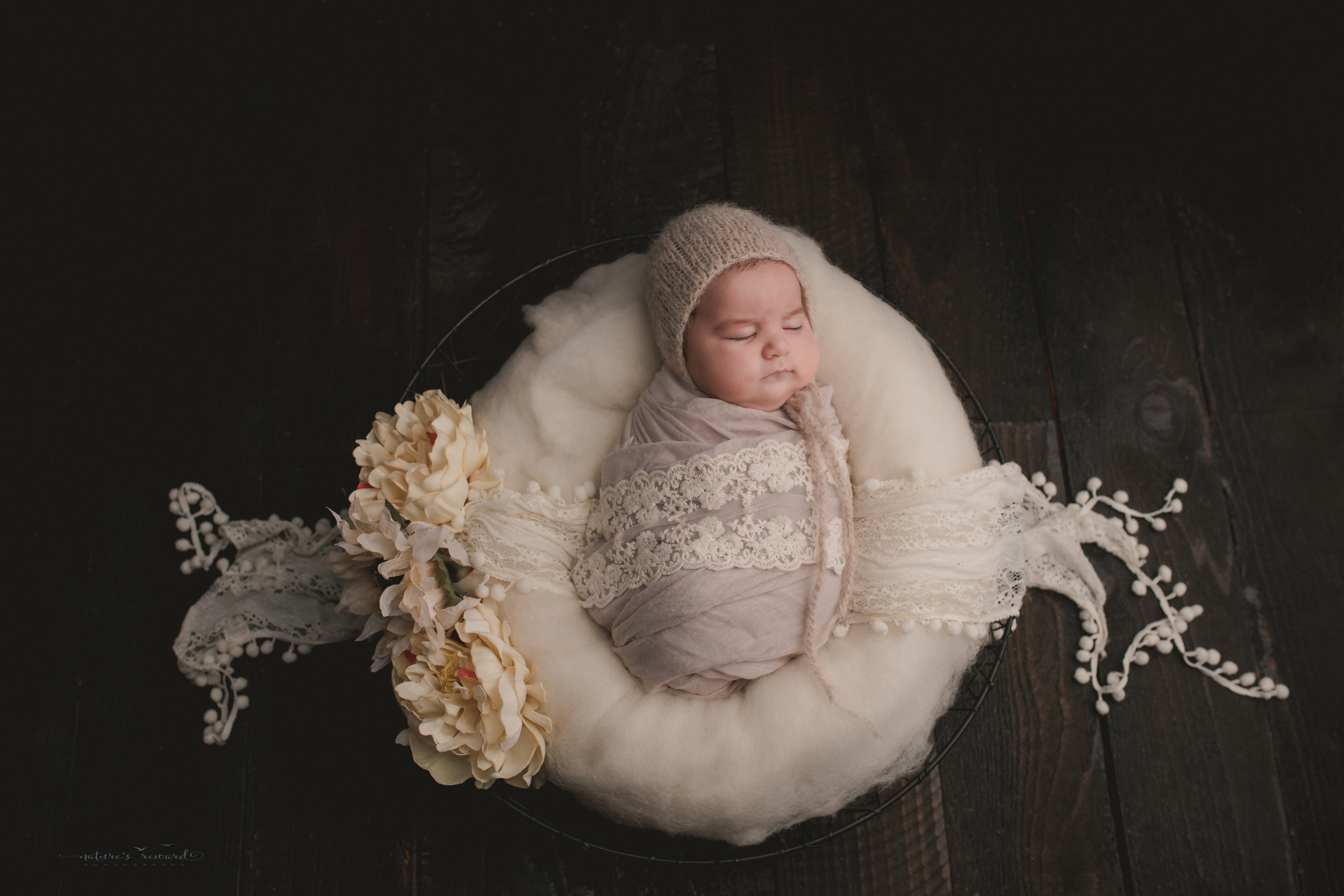 Dreaming, swaddled  in lace and fluff on a wood floor, a newborn portrait by Nature's Reward Photography