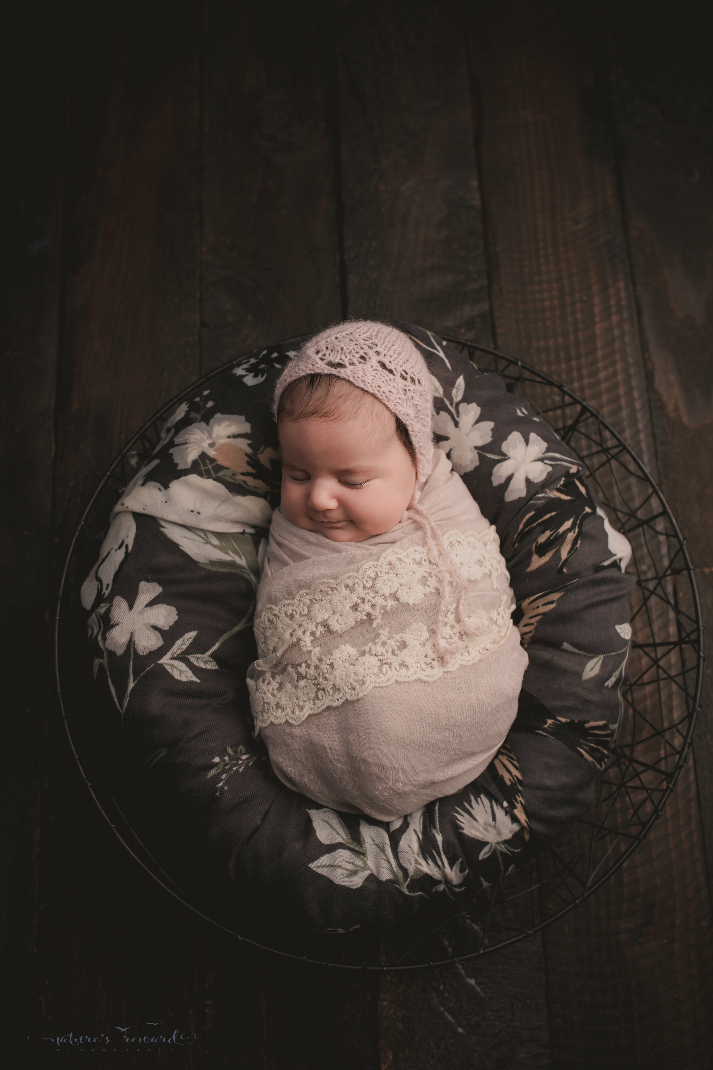 Dreaming, swaddled in lace and laying on grey floral on a wood floor, a newborn portrait by Nature's Reward Photography