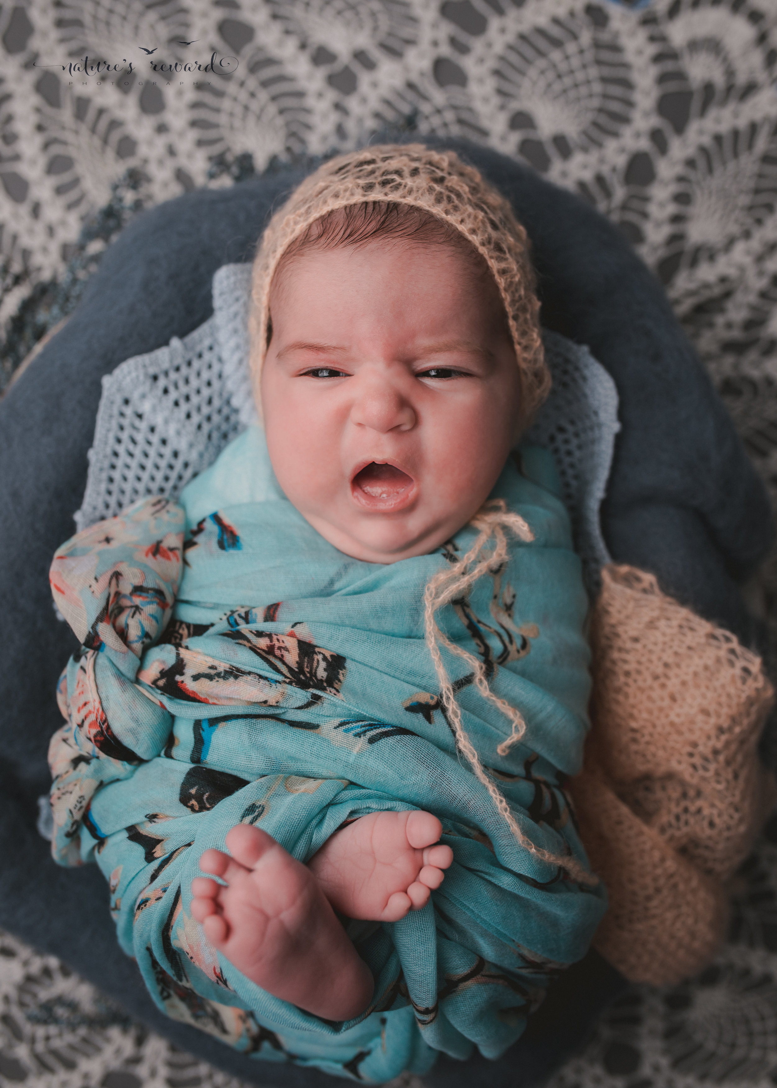 In blue floral and coral on vintage lace, she made this great face - a newborn portrait by nature's reward photography