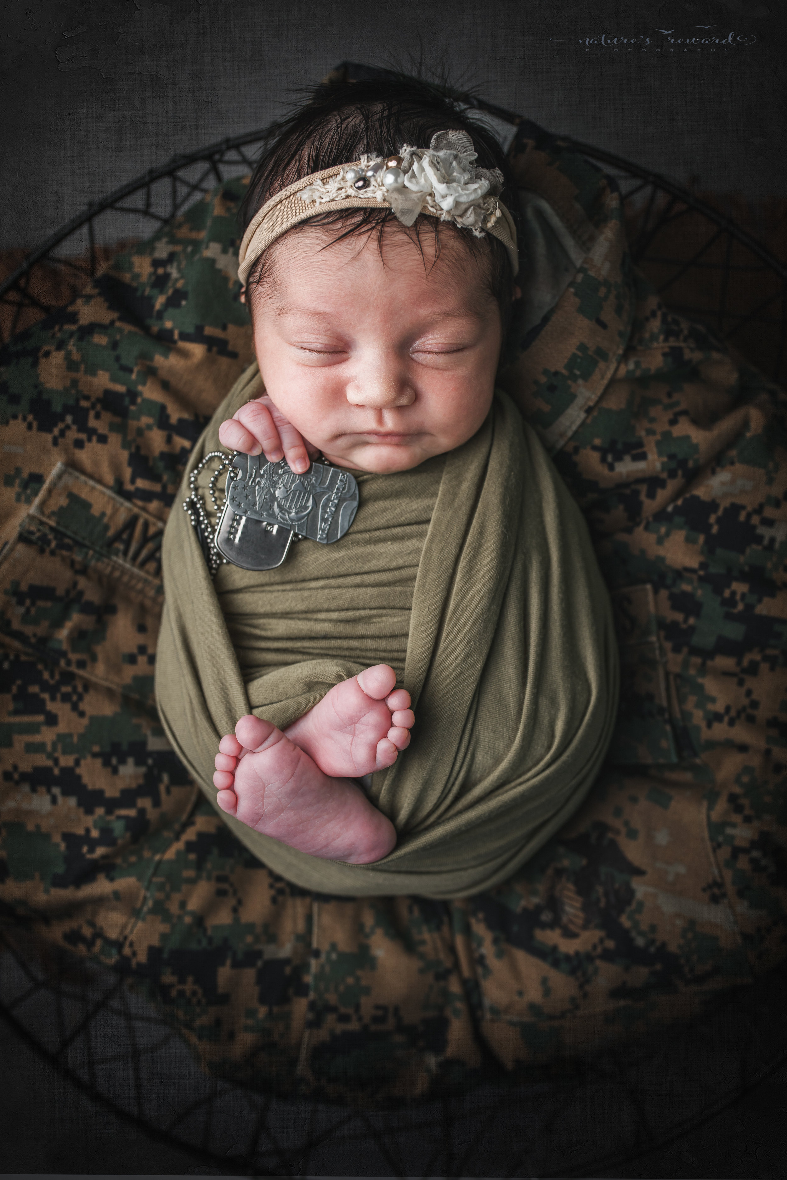 Newborn baby girl swaddled in army green laying on her father's service uniform with his dog tags, a portrait by Nature's Reward Photography