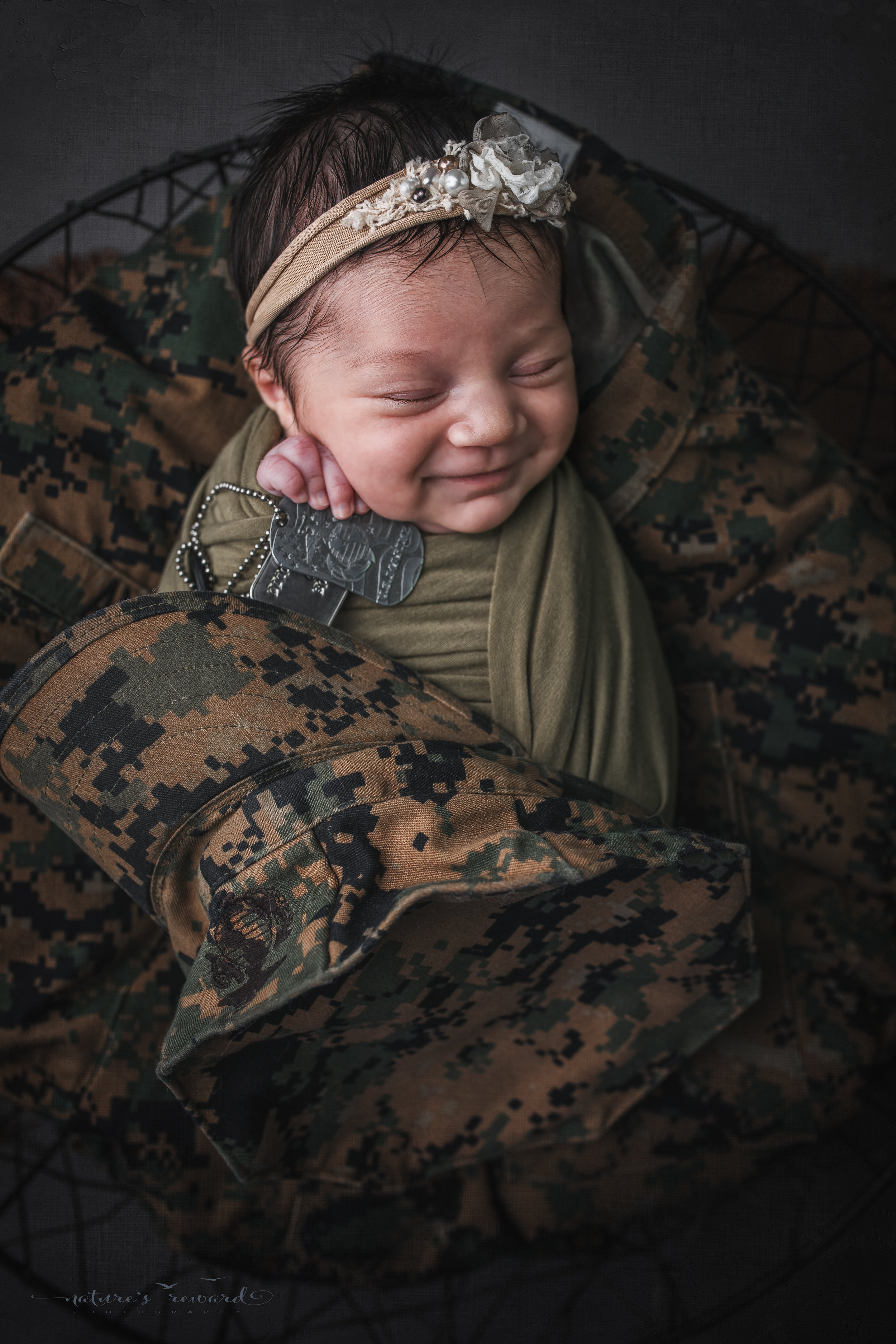 Newborn baby girl, smiling, swaddled in army green laying on her father's service uniform with his dog tags, a portrait by Nature's Reward Photography
