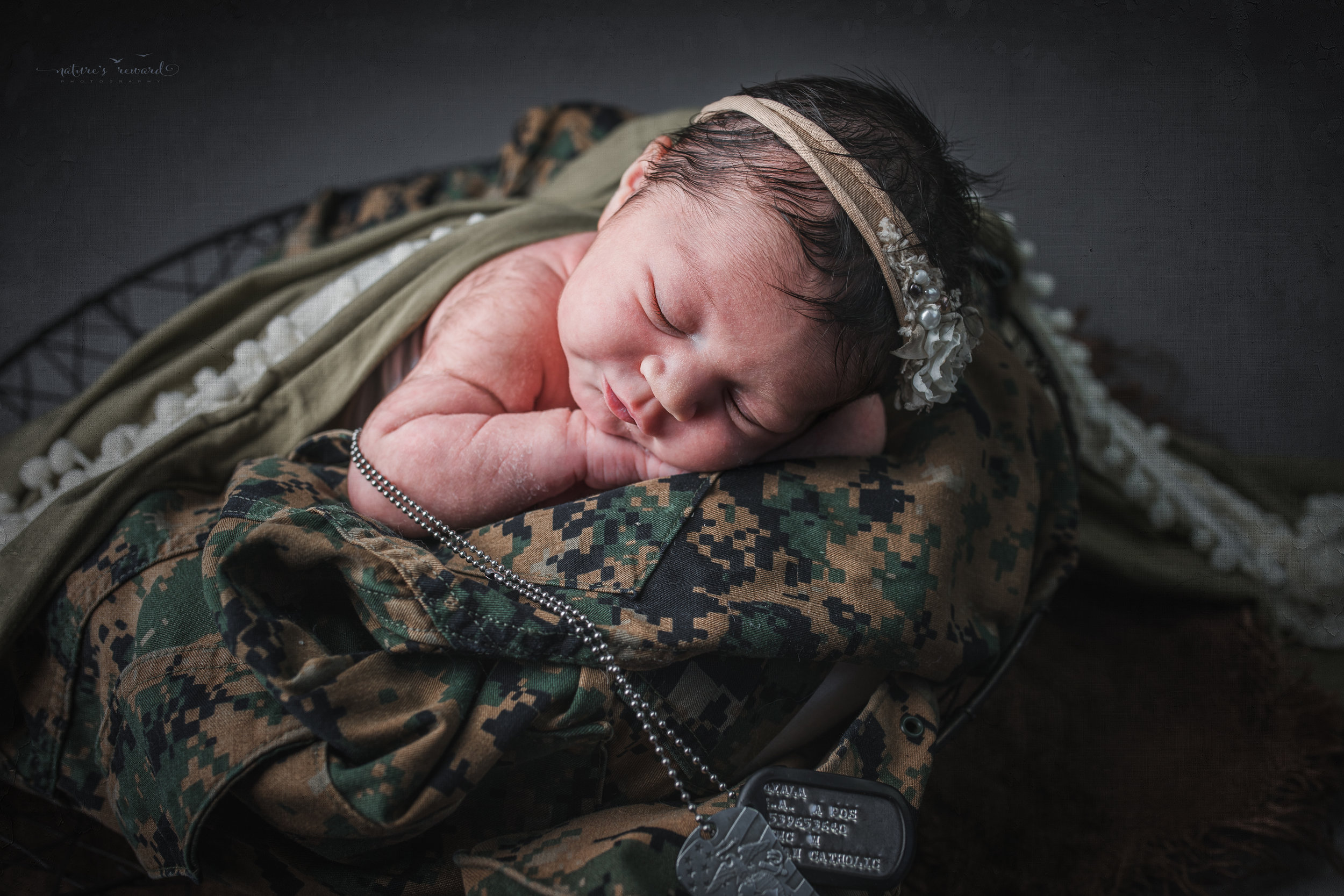 Newborn baby girl  in army green laying on her father's service uniform with his dog tags, a portrait by Nature's Reward Photography
