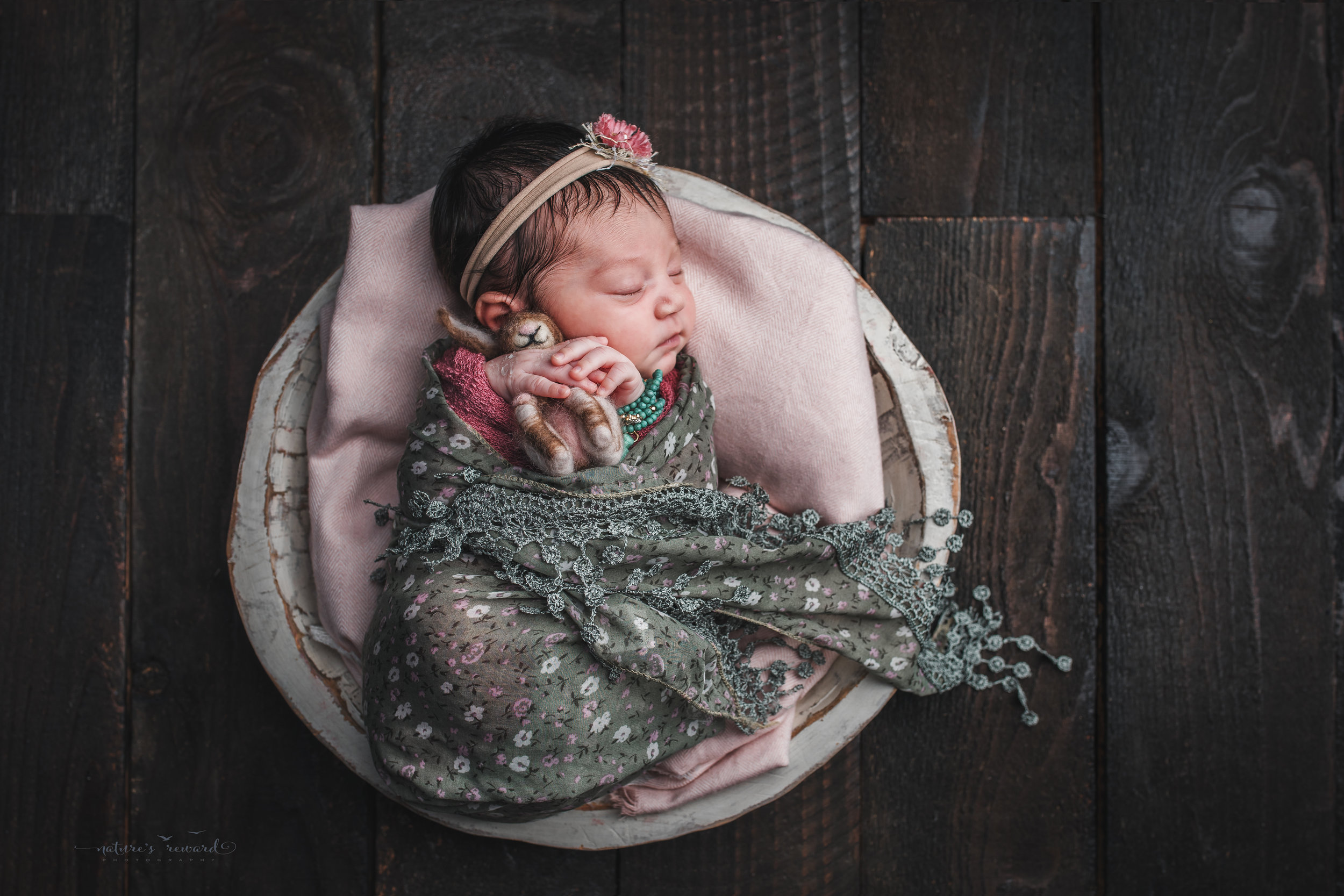 Newborn Baby girl in a wood bowl on a bed of pink wearing a floral green holding a bunny on a wood floor, a portrait by Nature's Reward Photography