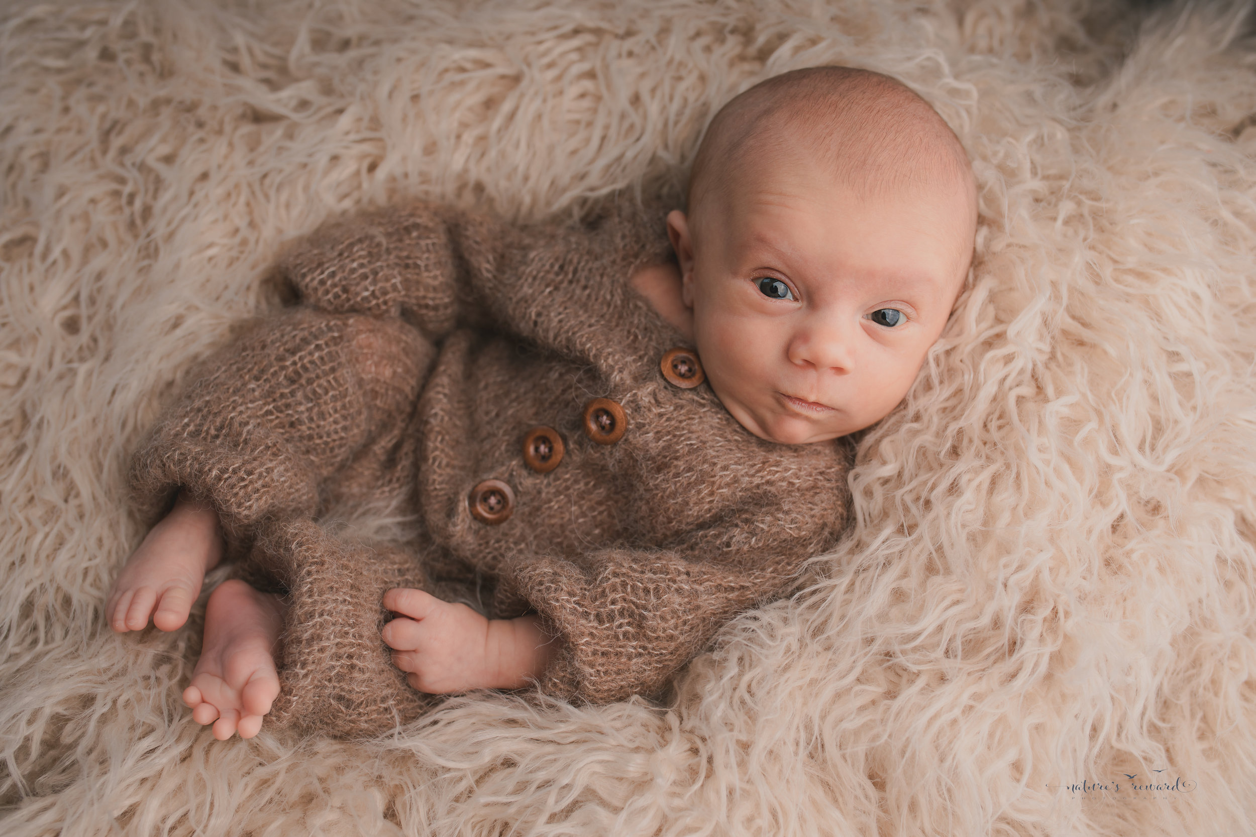 A baby boy wearing a sleeper on a tan fur making a great face by nature's Reward Photography