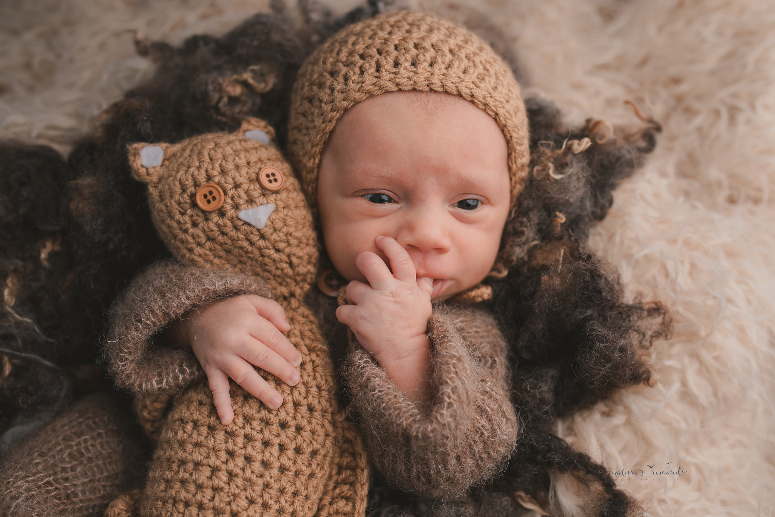A baby boy wearing a sleeper and tan bonnet holding a teddy on a tan fur making a great face by nature's Reward Photography
