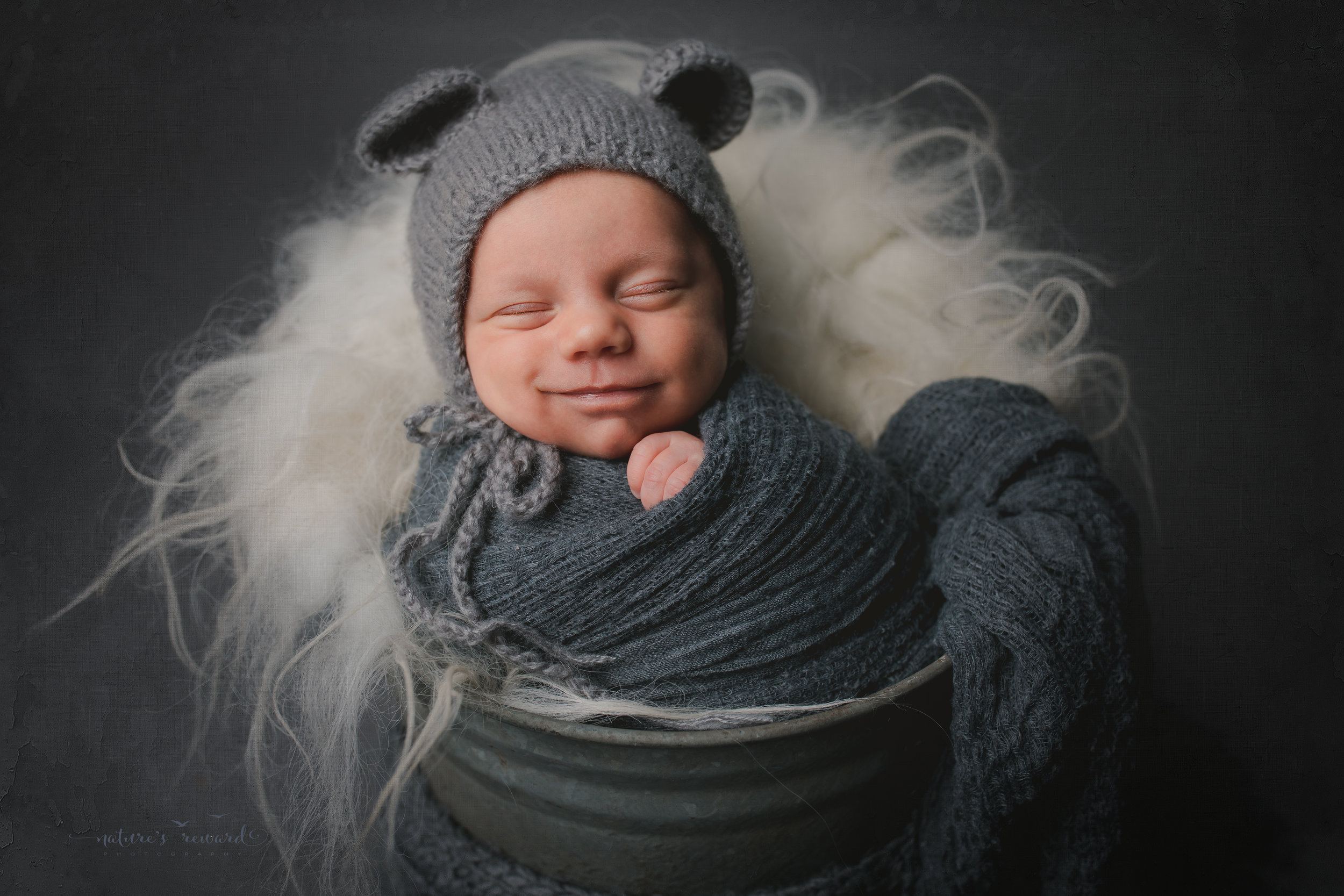 A baby boy in a bucket wearing a bear bonnet , smiling- a portrait by Nature's Reward Photography