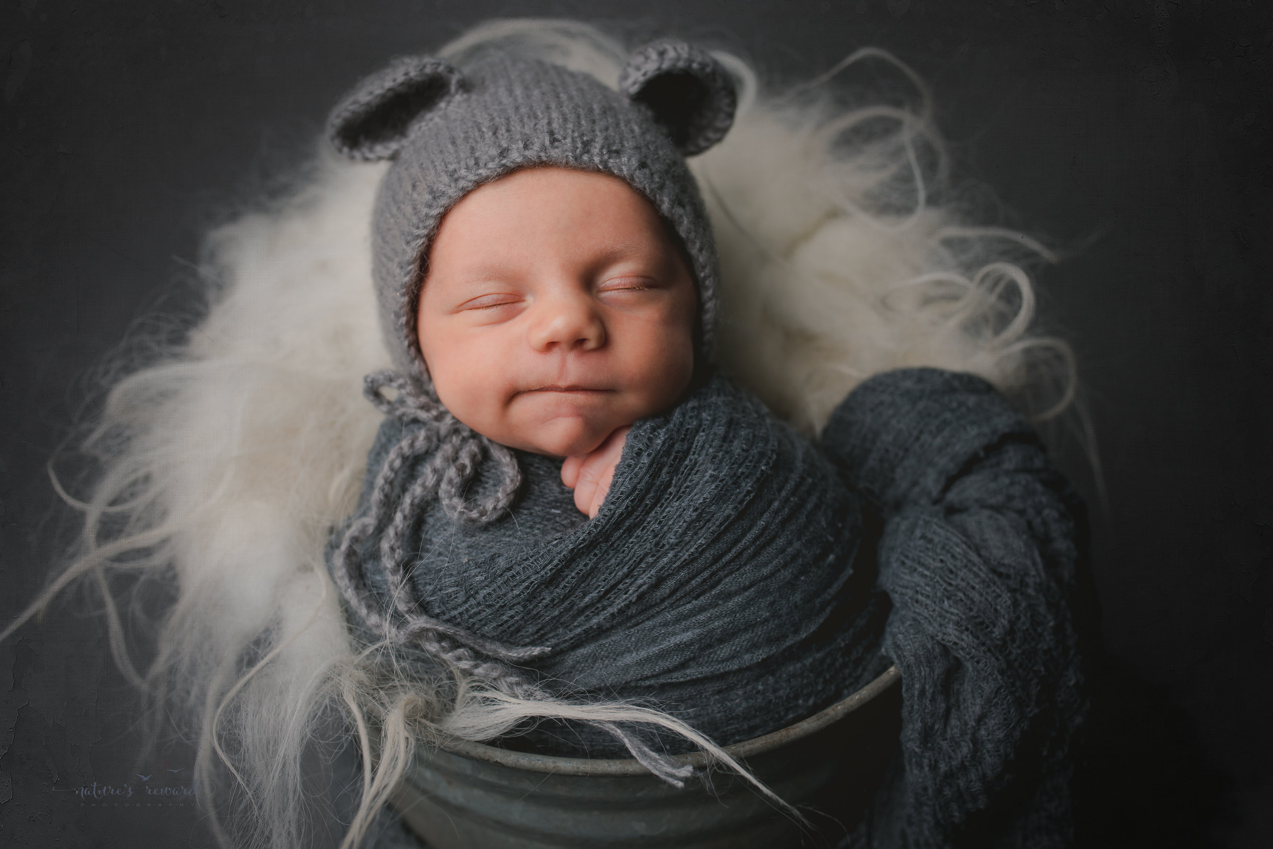A baby boy in a bucket wearing a bear bonnet , grinning- a portrait by Nature's Reward Photography