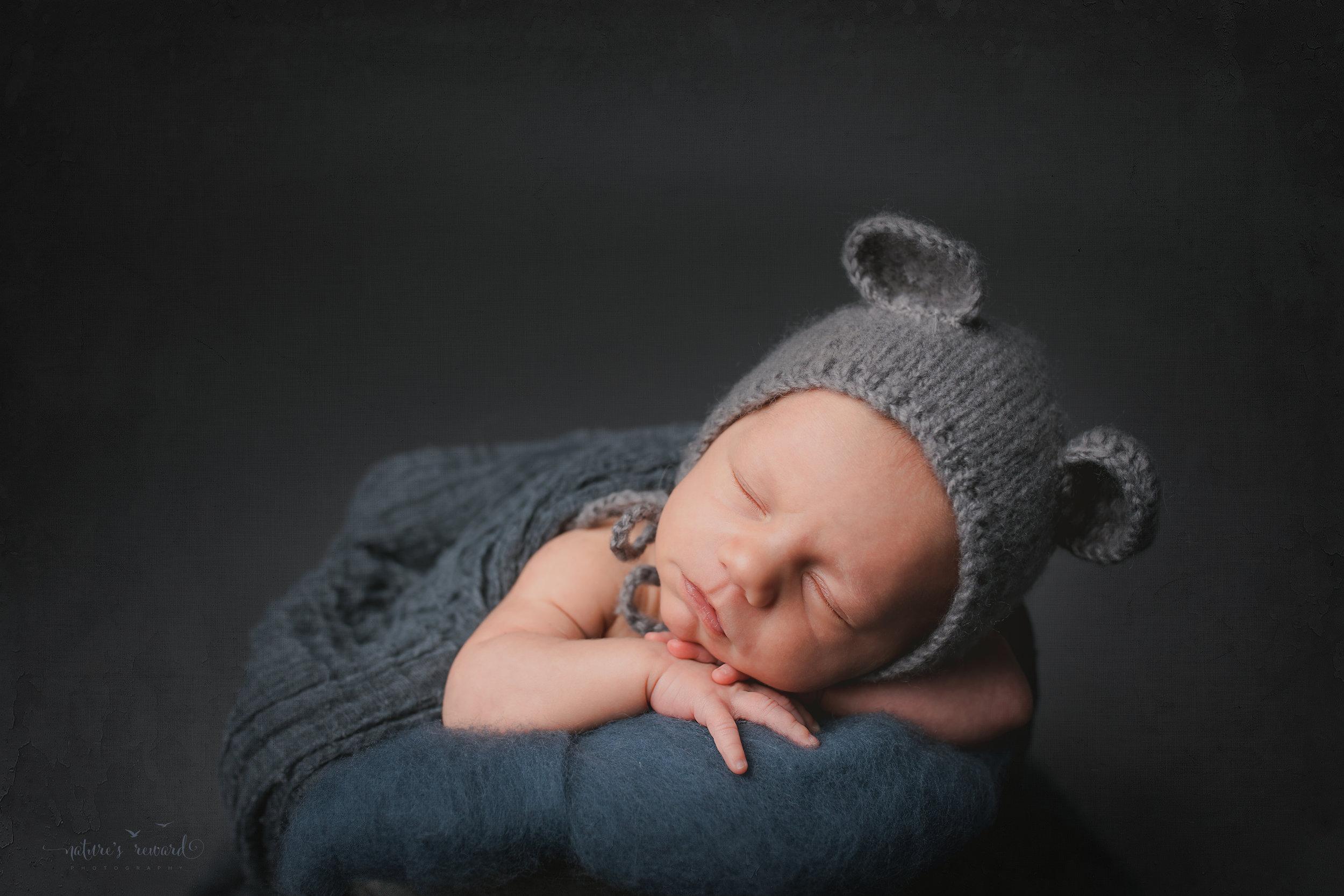 A baby boy in a bucket wearing a bear bonnet- a portrait by Nature's Reward Photography