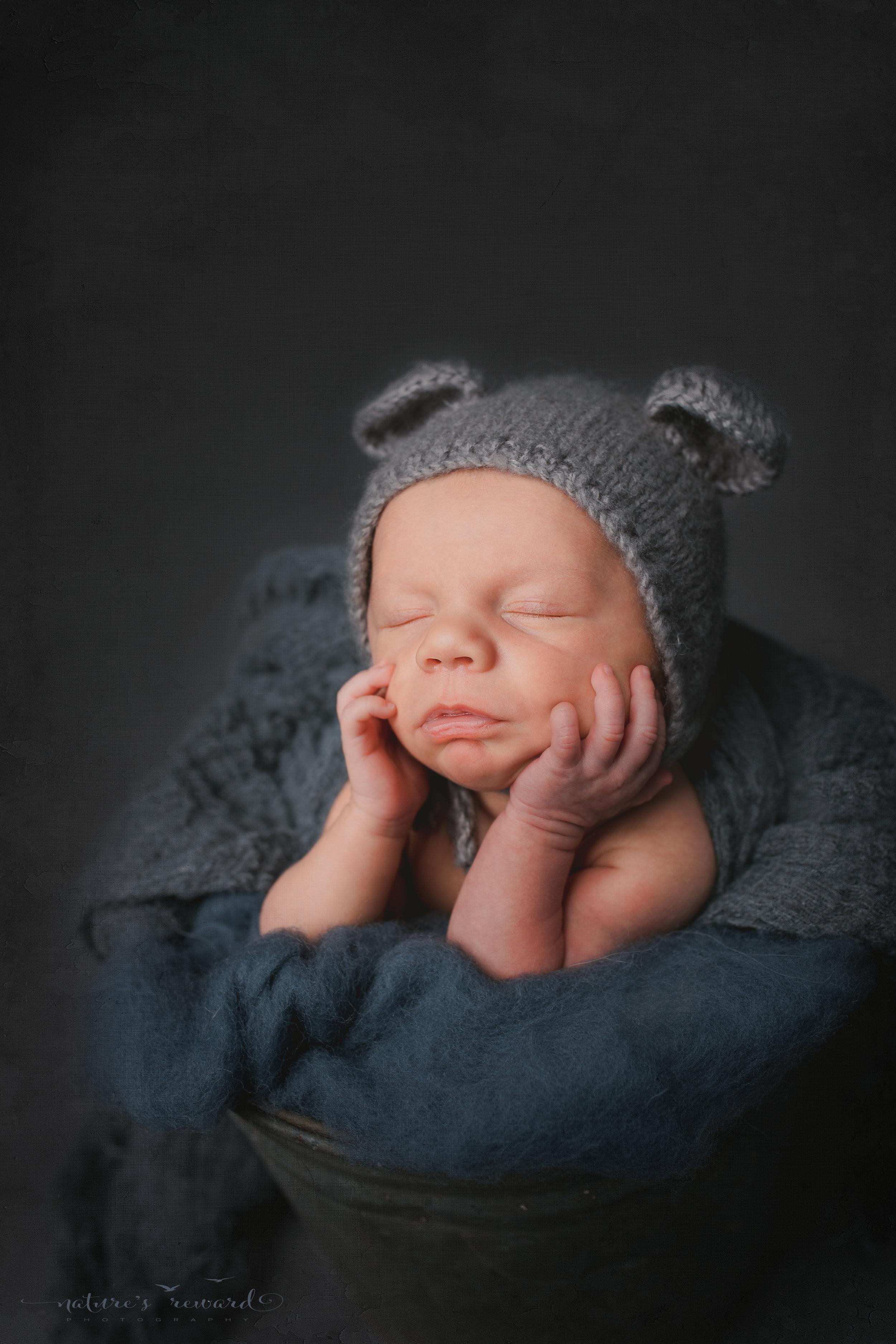 A baby boy in a bucket wearing a bear bonnet - a portrait by Nature's Reward Photography