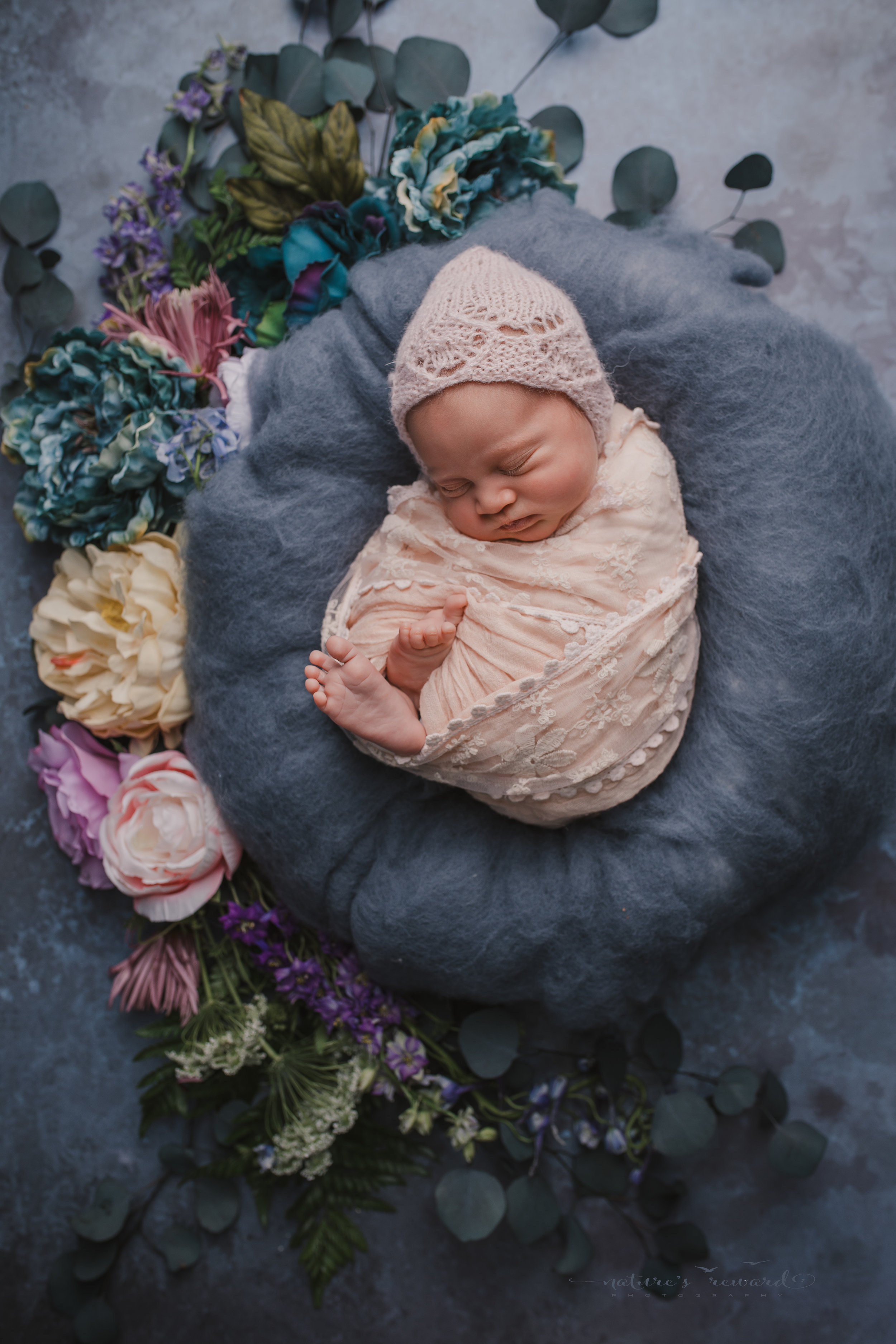 Newborn baby Girl swaddled in pink with her toes showing on a blue and grey floral backdrop surrounded by colorful flowers in this baby portrait by Nature's Reward Photography