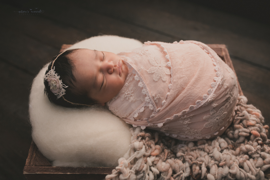 Newborn Baby girl wrapped in pink lace and sitting in a wooden box on a real wood floor in a stunning portrait by Nature's Reward Photography