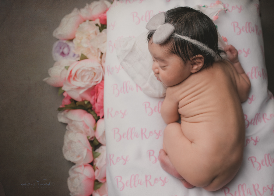 Newborn baby girl on a bed with her name written in the sheet surround by flowers in this portrait by Nature's Reward Photography