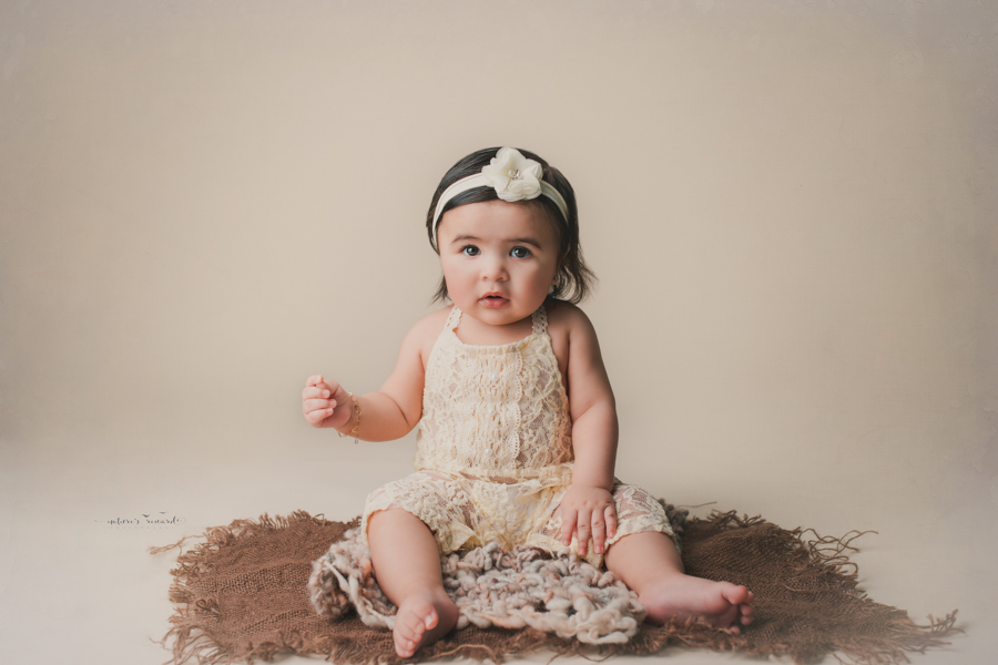 Sweet 6 month old baby girl in a sitter portrait wearing a lace romper by Nature's Reward Photography