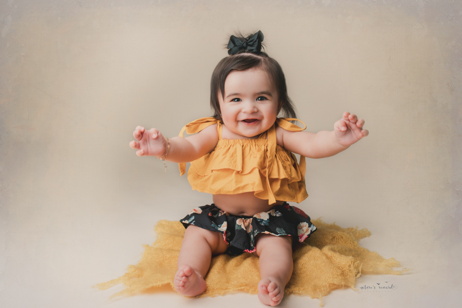 Darling 6 month old baby girl in a cute outfit showing off that tummy in a portrait by nature's Reward Photography