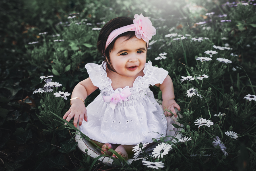 Sweet 6 month old baby girl in a summer white dress in the spring flower garden a portrait by Nature's Reward Photography
