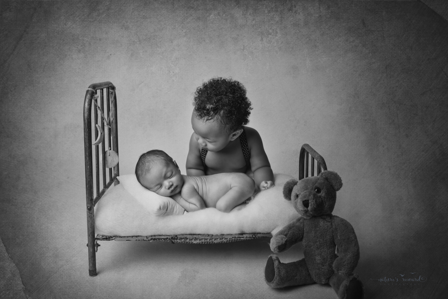 Black and white portrait of newborn baby boy laying in a bed in a bum up pose while his big brother looks lovingly at him in a newborn portrait by Nature's Reward Photography