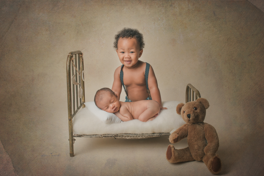 Newborn baby brother laying on a bed and his young big brother smiles excitedly in a newborn portrait by Nature's Reward Photography
