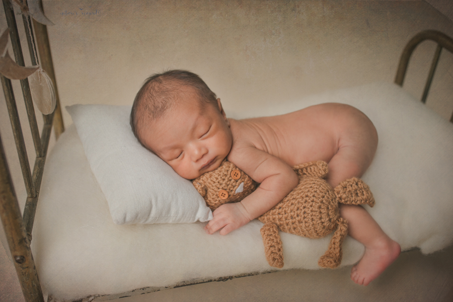Newborn baby boy bum up with a leg dangling off the bed holding a teddy in a newborn portrait by Nature's Reward Photography