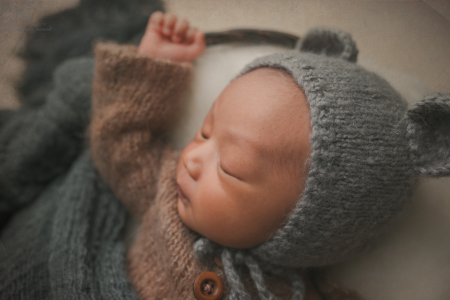 Newborn baby boy in a basket of fluff wearing a darling brown sleeper wearing a grey bear bonnet in a newborn portrait by Nature's Reward Photography