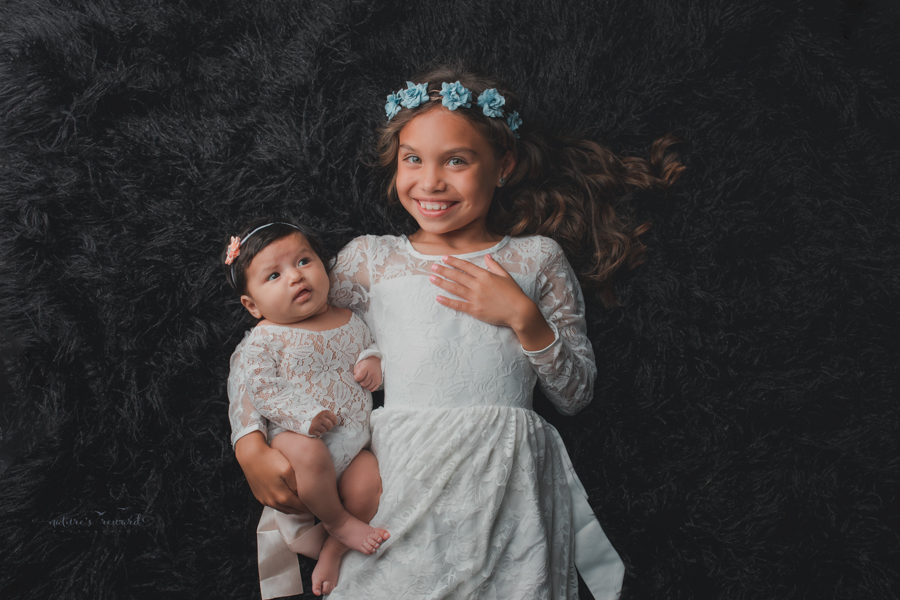 Newborn baby girl and big sister in newborn portrait by Nature's Reward Photography.