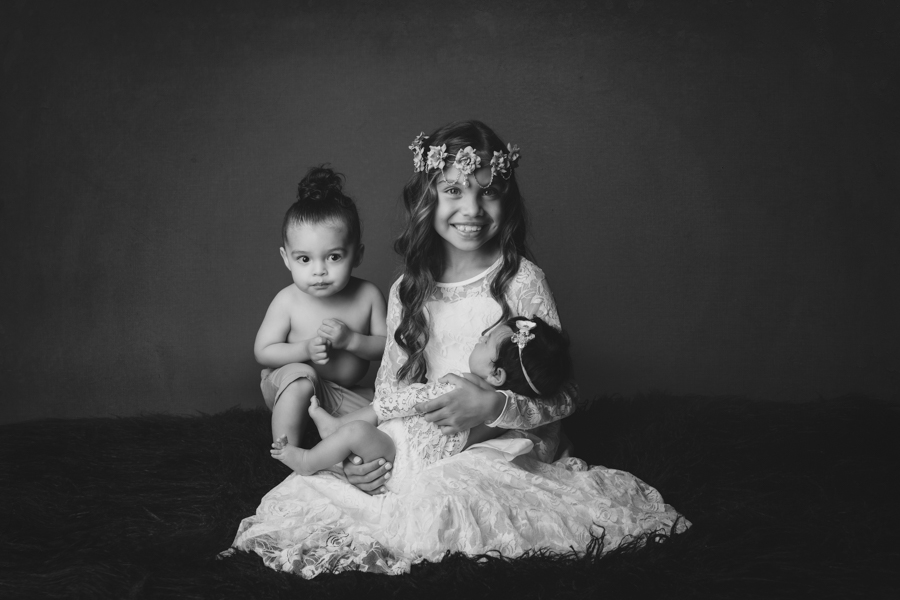 Black and white image of Newborn baby girl and her big brother and big sister in newborn portrait by Nature's Reward Photography.